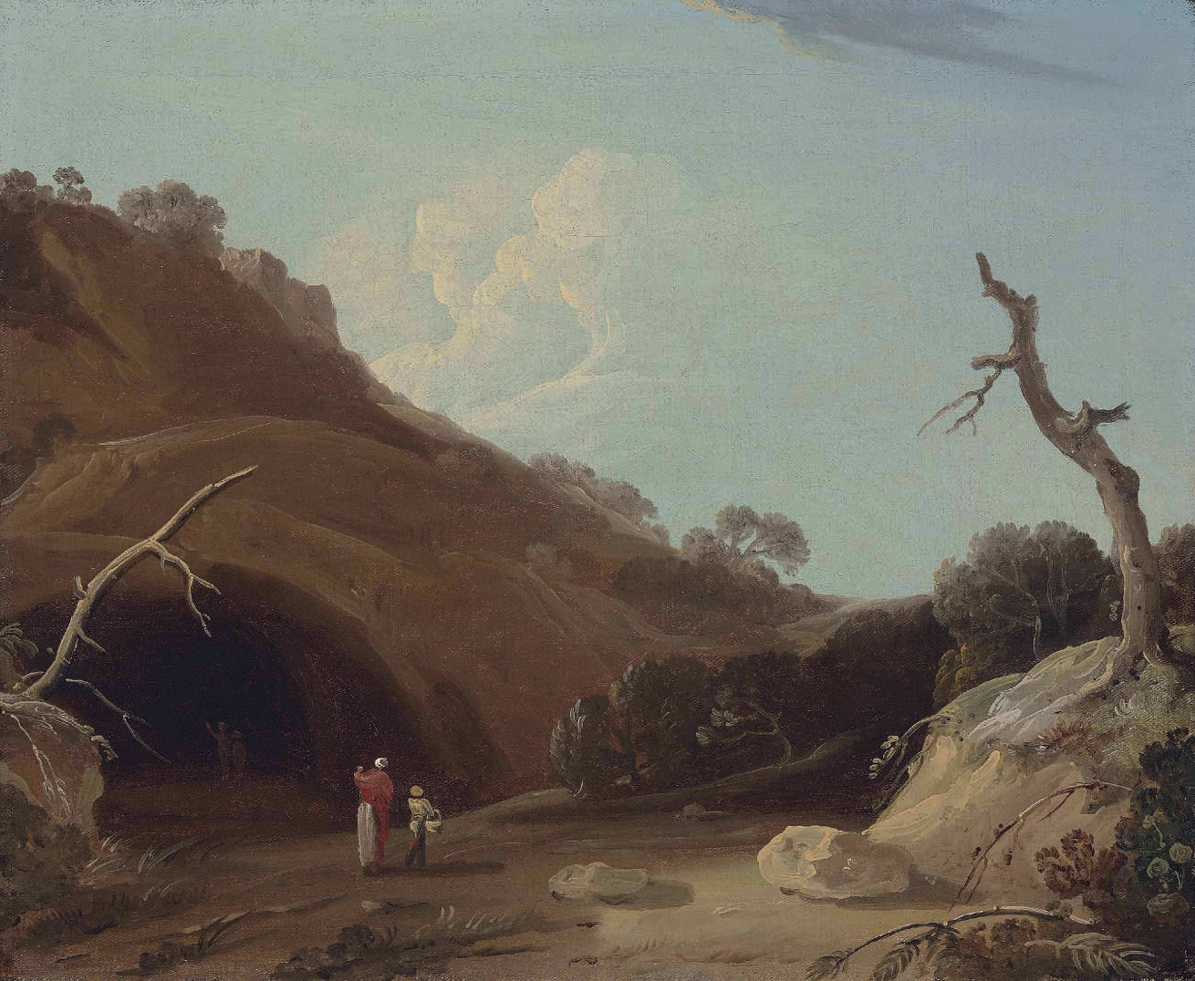 A hilly Indian landscape with figures passing by a cave