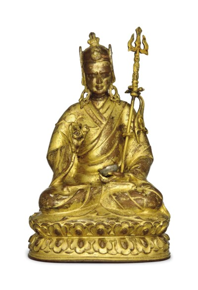 A GILT COPPER SEATED FIGURE OF