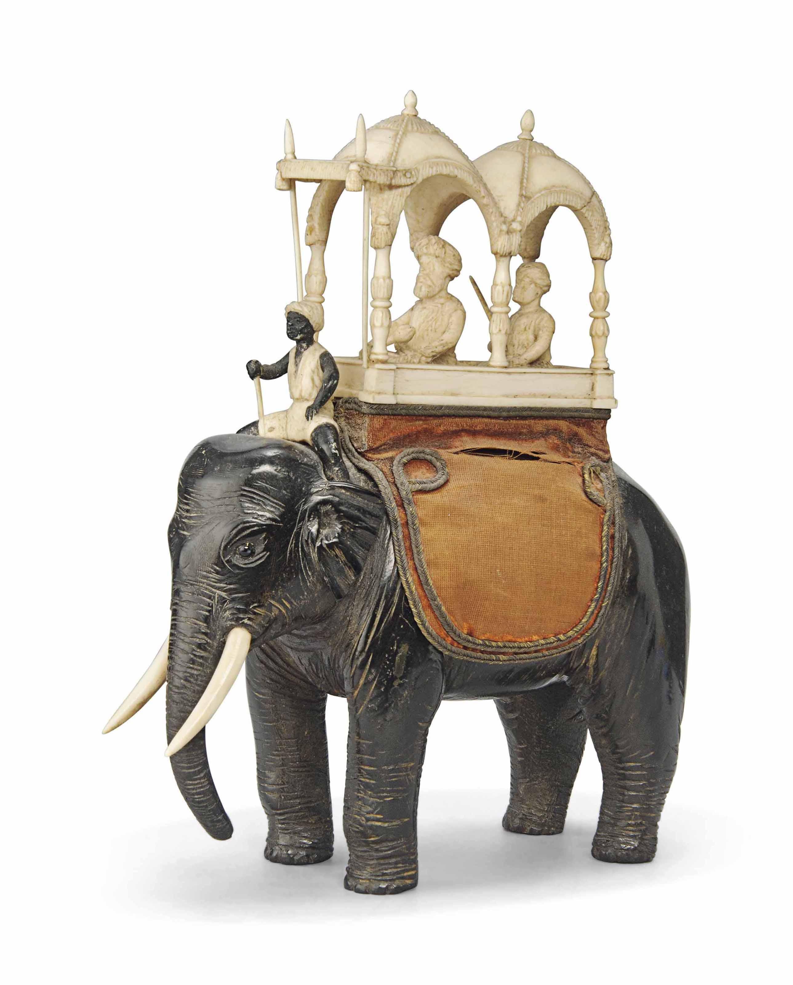 AN INDIAN IVORY MOUNTED EBONY ELEPHANT AND HOWDAH GROUP