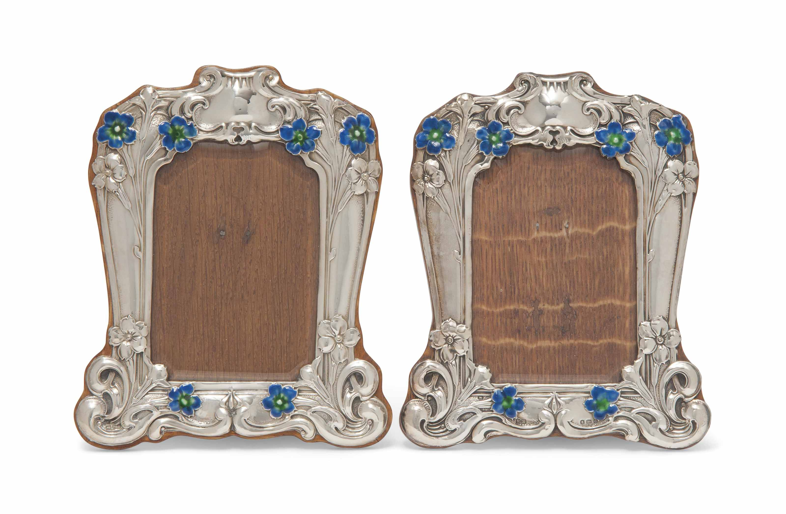 A MATCHED PAIR OF EDWARDIAN SILVER AND ENAMEL PHOTOGRAPH FRAMES