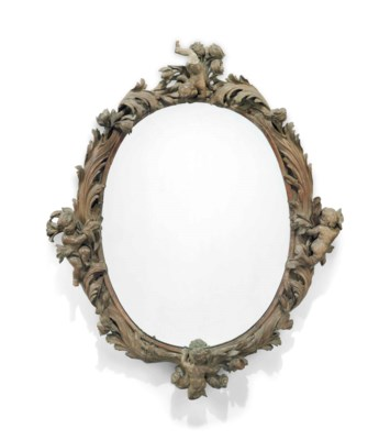 A LARGE CARVED OVAL MIRROR