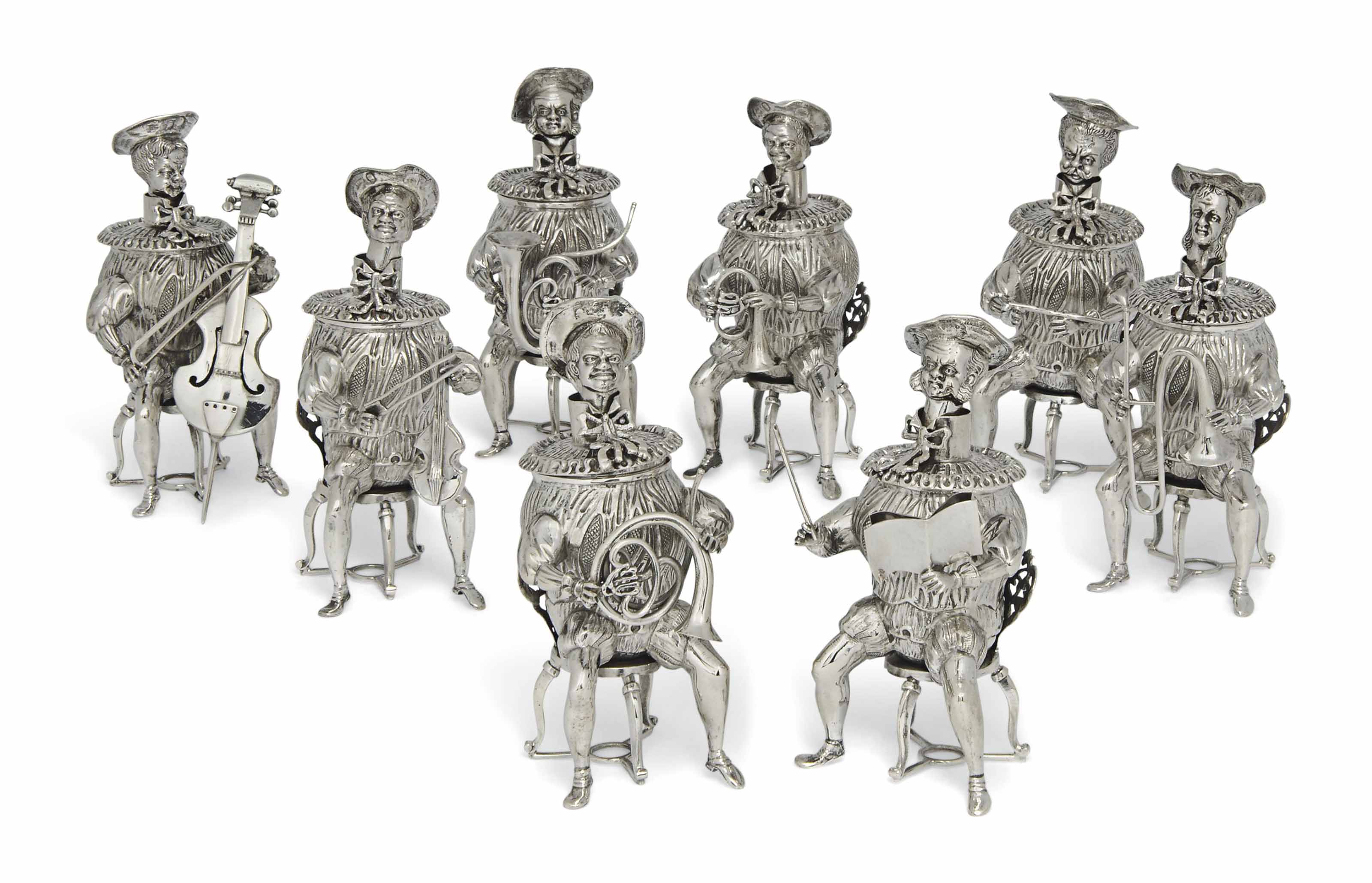 A BAND OF EIGHT GERMAN SEATED SILVER MUSICIAN TABLE ORNAMENTS