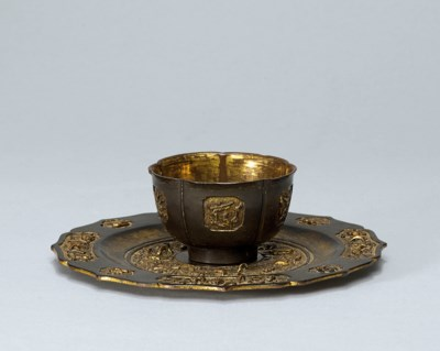 A PARCEL GILT BRONZE CUP AND S