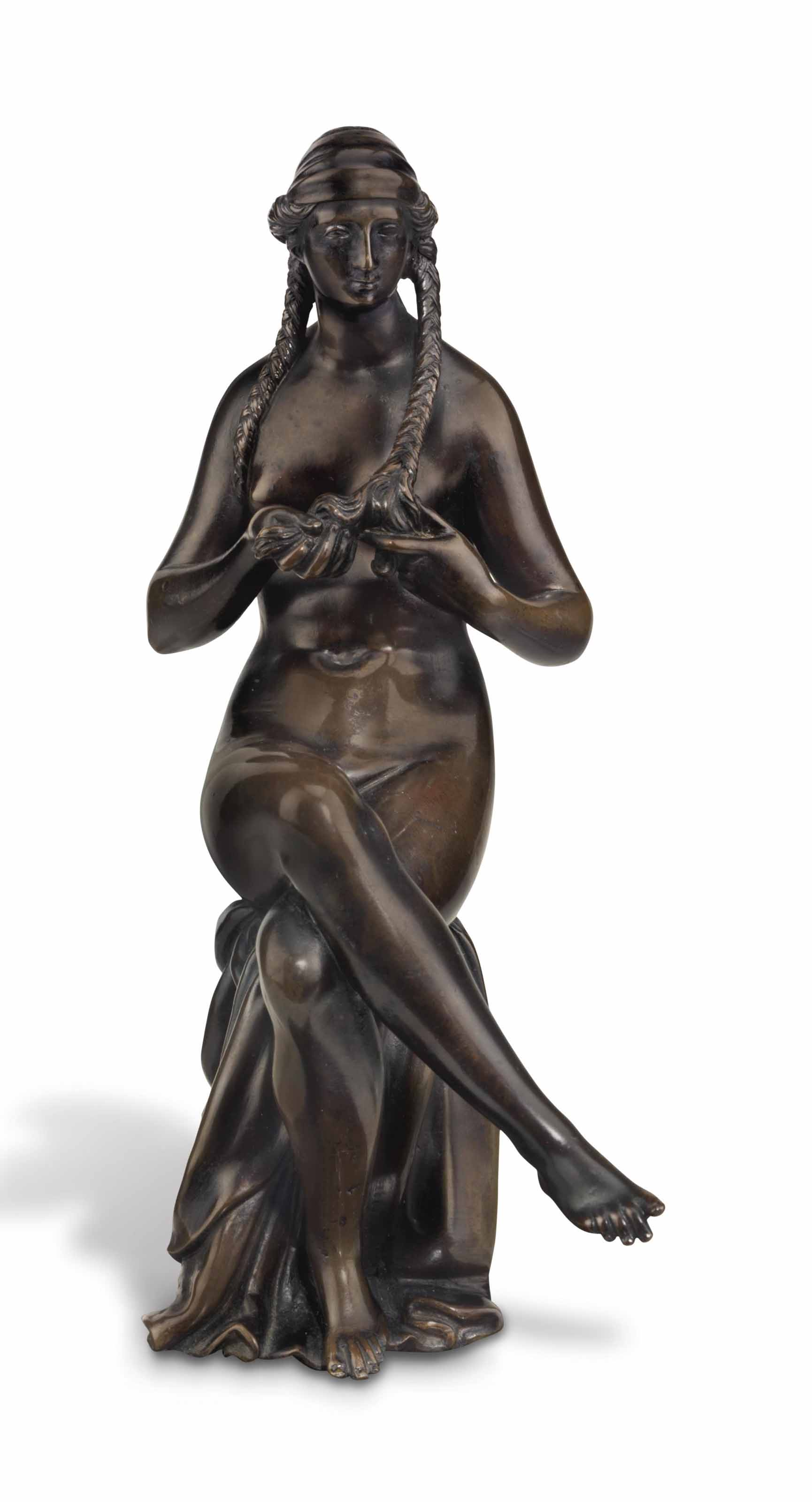 A BRONZE FIGURE OF A SEATED NUDE WOMAN BRAIDING HER HAIR