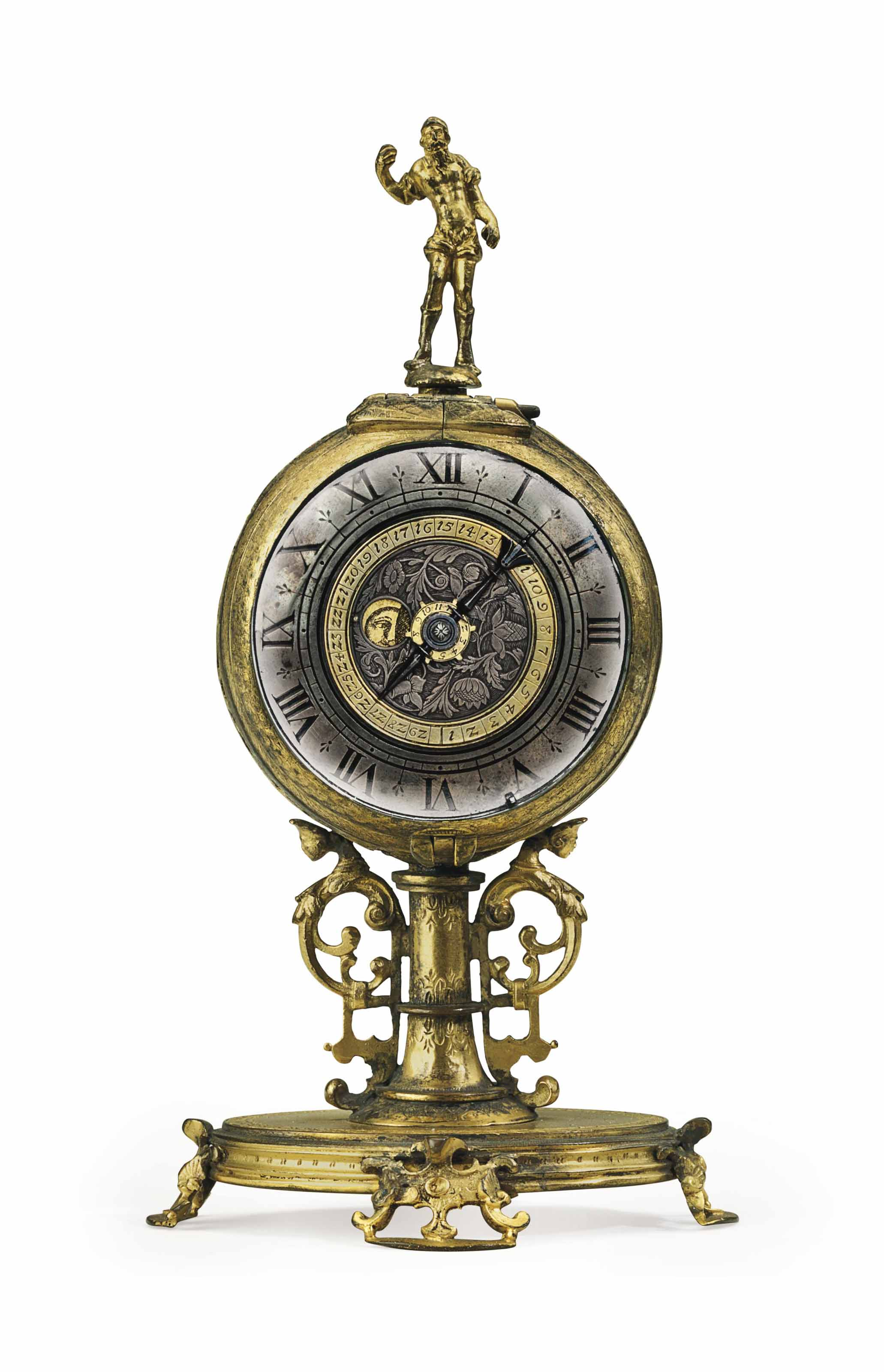A GERMAN MINIATURE PIERCED AND ENGRAVED GILT-BRASS STRIKING TABLE CLOCK WITH ALARM AND MOONPHASE
