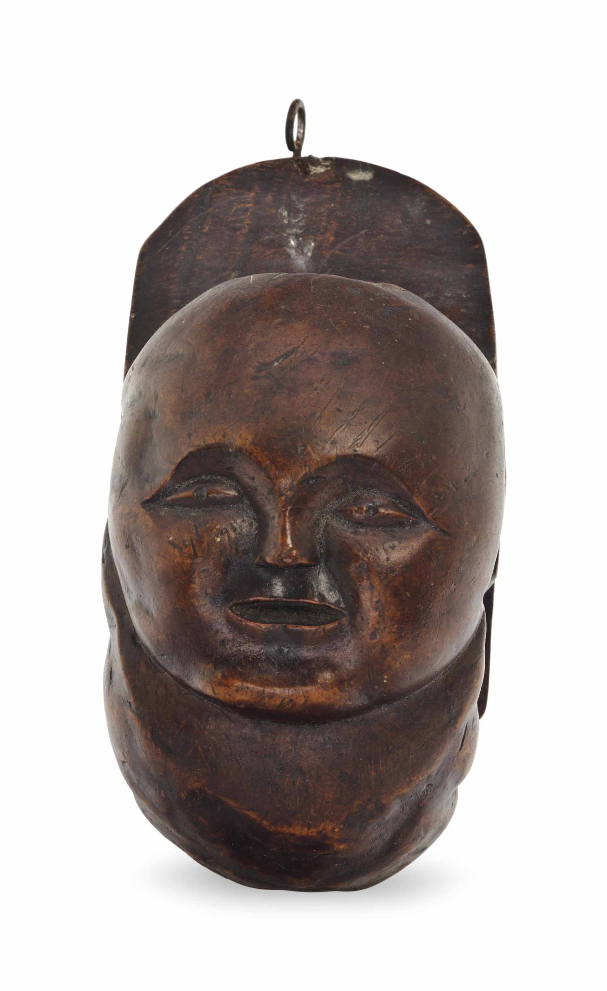 A ROOT CARVING OF A FACE,