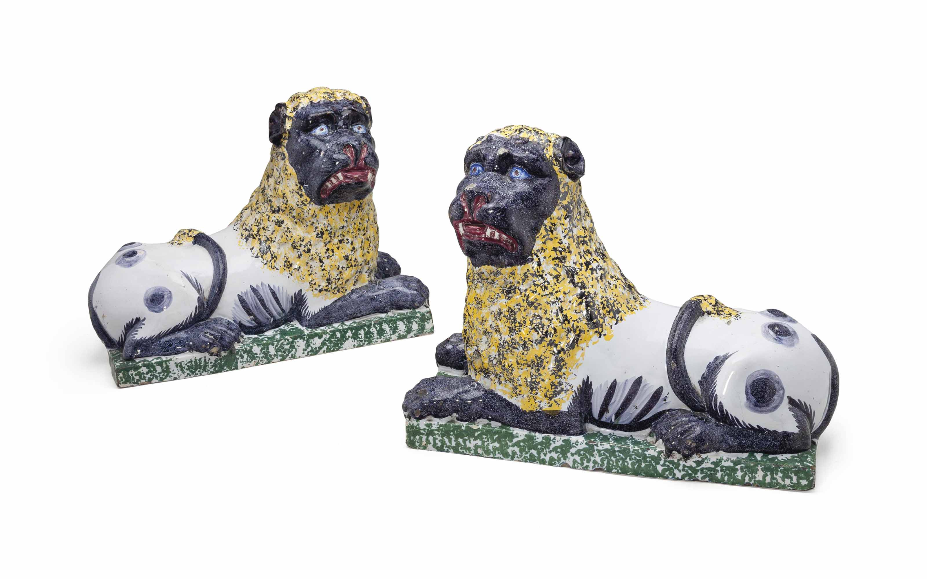 A LARGE PAIR OF FRENCH FAIENCE MODELS OF RECUMBENT LIONS