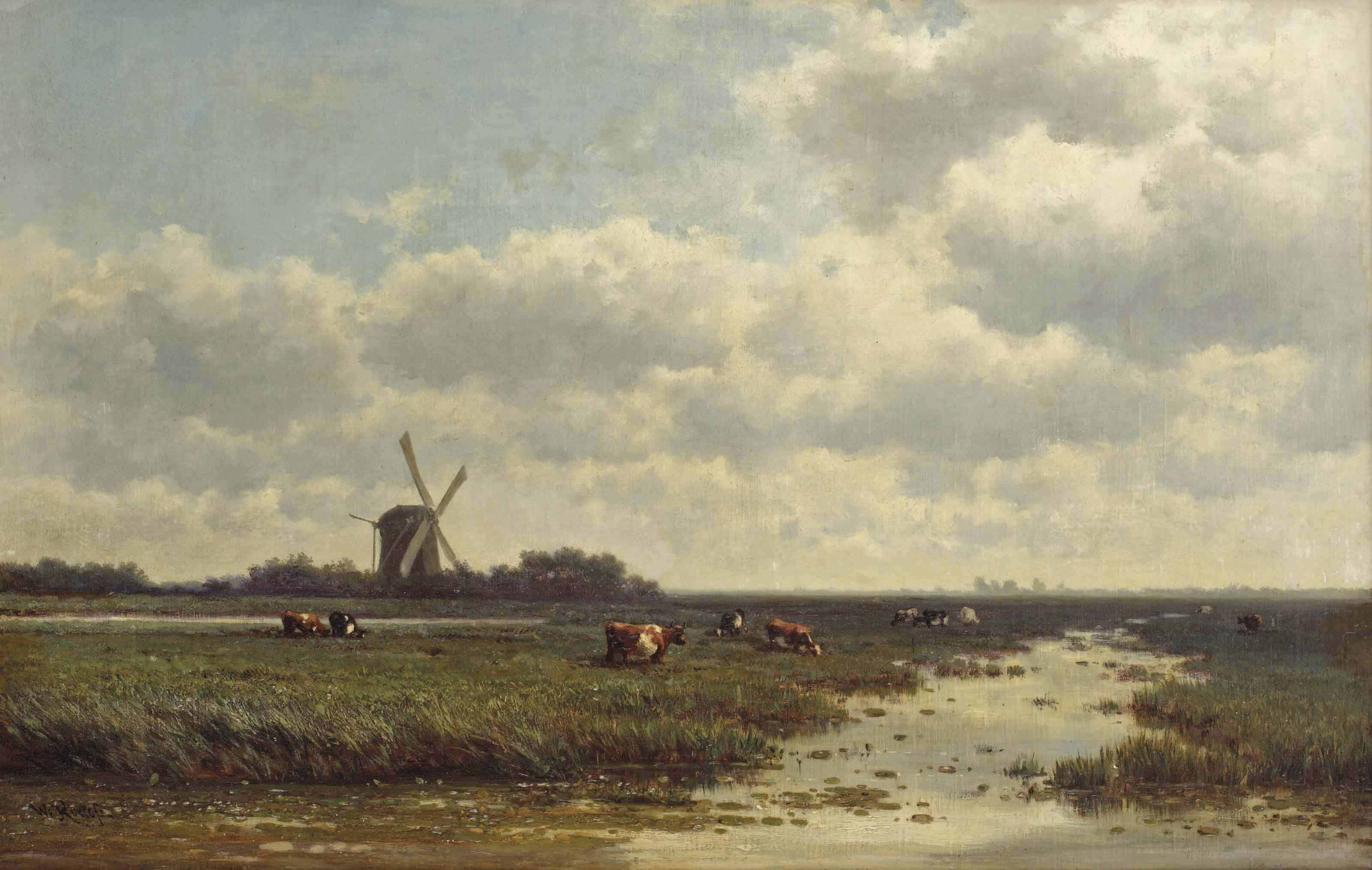 Cows grazing near a windmill