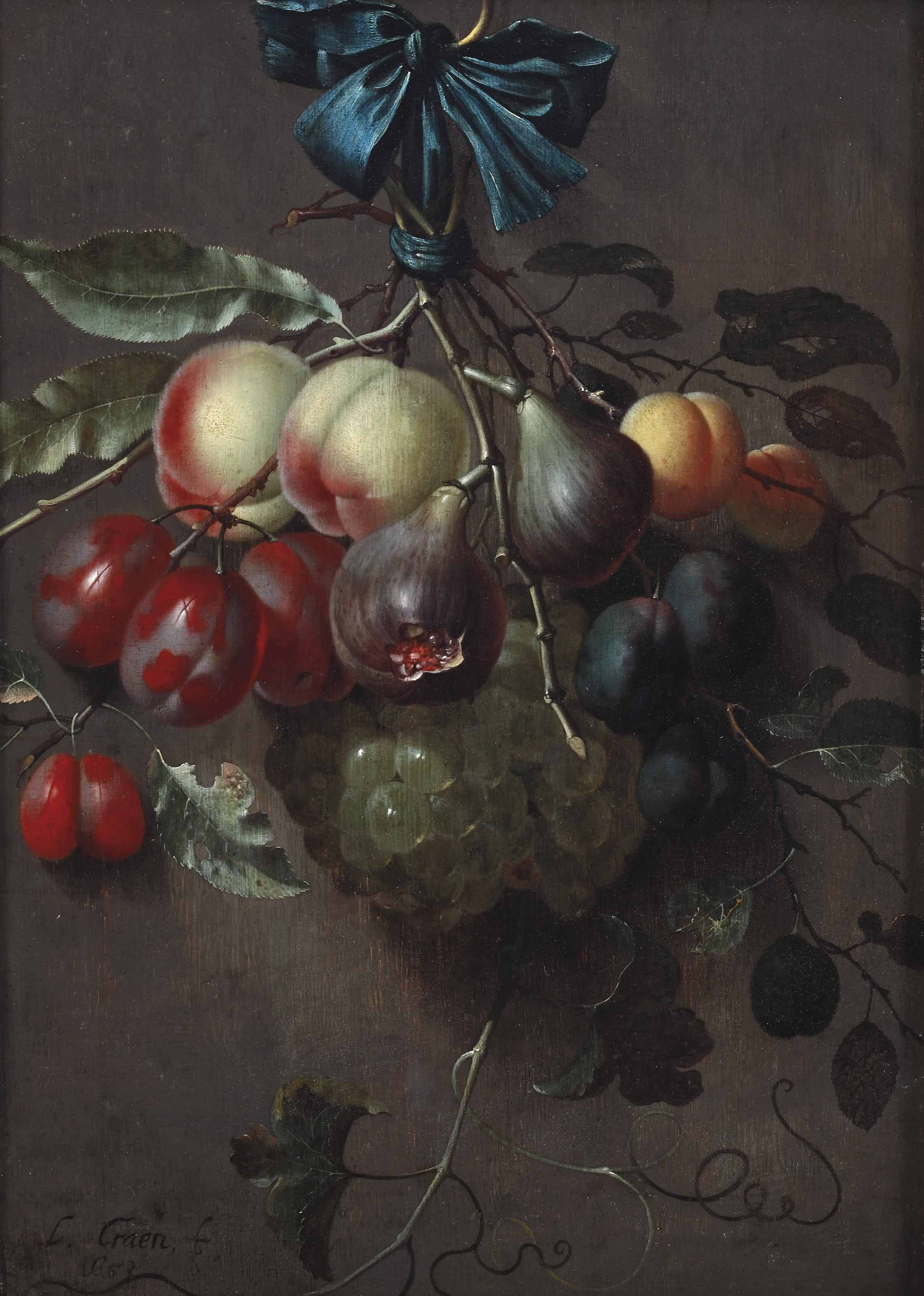 Peaches, plums, figs, apricots, dates and grapes hanging from a blue ribbon tied to a hook