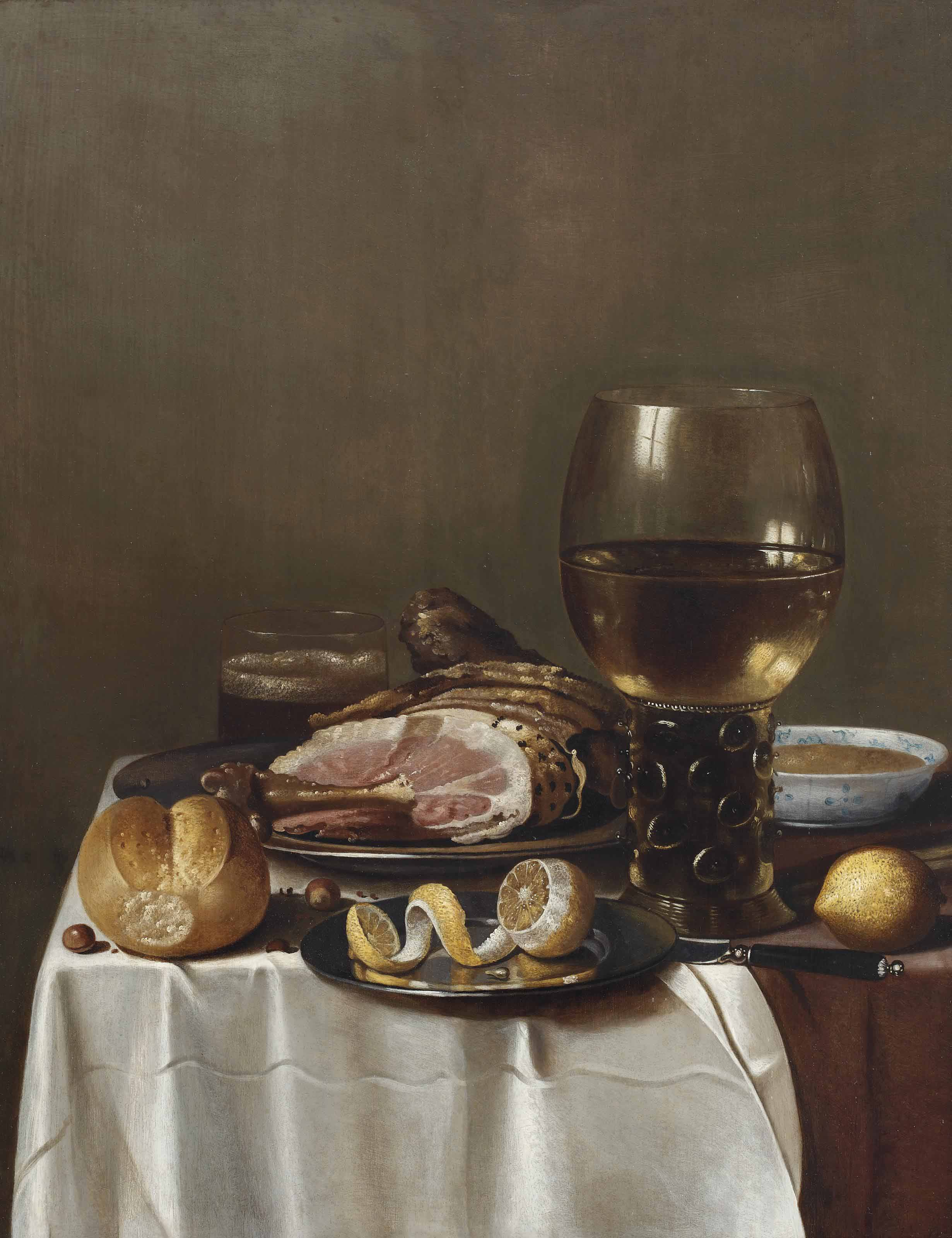 A roemer of white wine, a porcelain bowl, a ham, a glass of beer, a bread roll. a peeled lemon on a plate with a knife, on a partially draped table