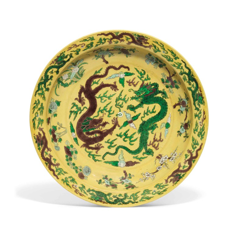 A large yellow-ground green and aubergine-enamelled dragon dish. Kangxi six-character mark in underglaze blue. 16⅛ in (41 cm) diam. This lot was offered in Chinese Ceramics & Works of Art  on 8 November 2016 at Christie's in London and sold for £161,000