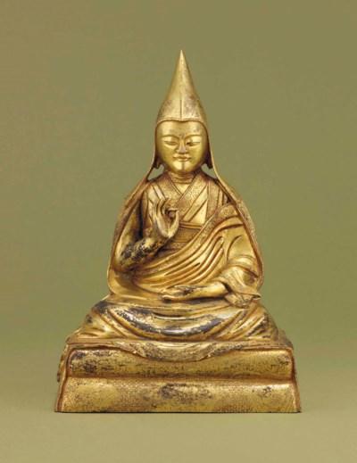 A GILT-BRONZE FIGURE OF A LAMA