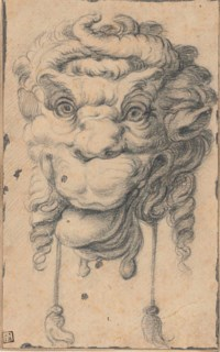 A grotesque head with horns and protruding tongue