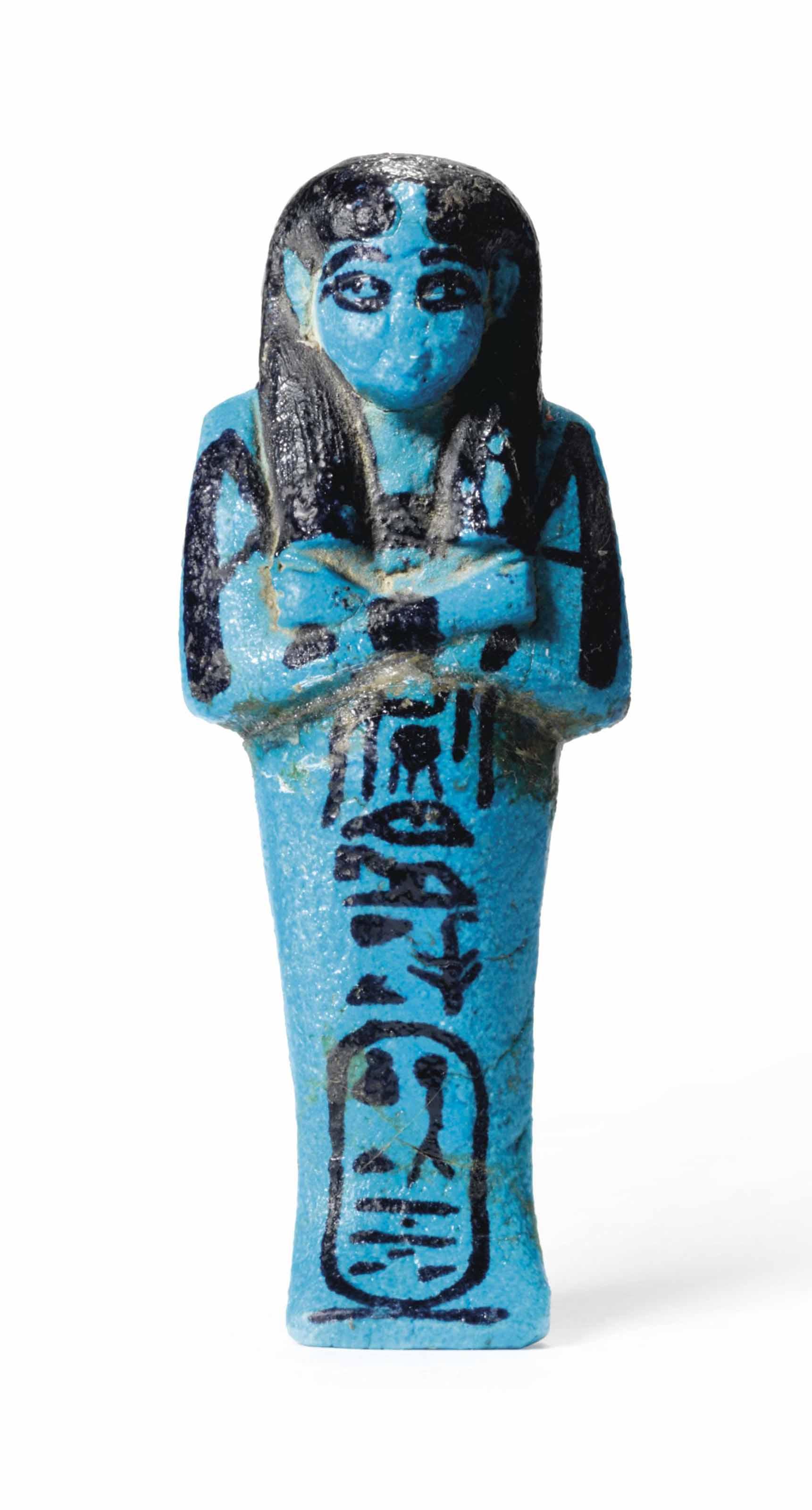 AN EGYPTIAN BLUE FAIENCE SHABTI FOR QUEEN HENUTTAWY