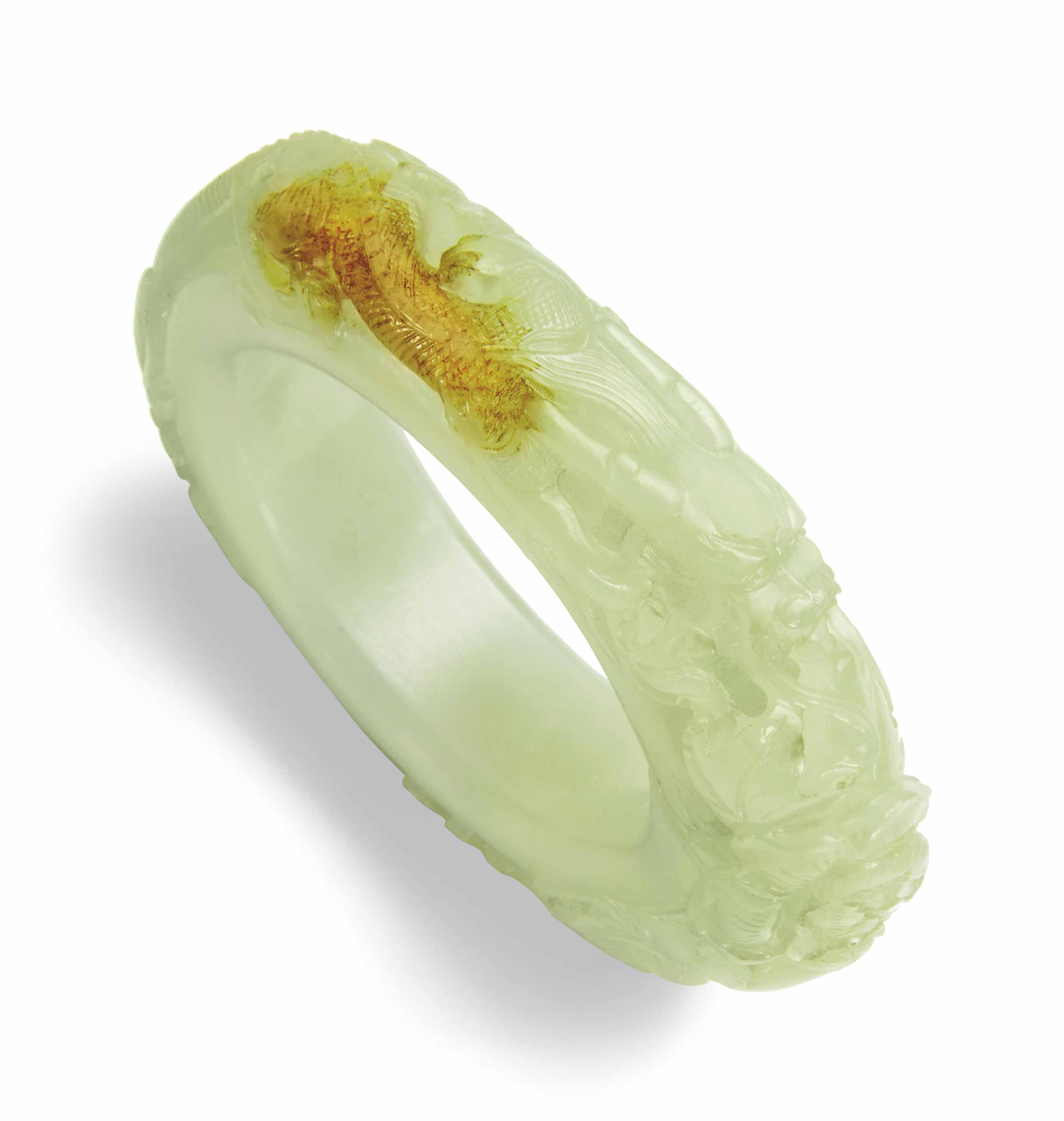 A WHITE AND RUSSET JADE 'DRAGON AND PHOENIX' BANGLE