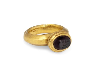 A GOLD AND GARNET RING WITH IN