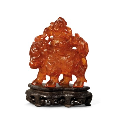 AN AMBER CARVING OF A BOY AND