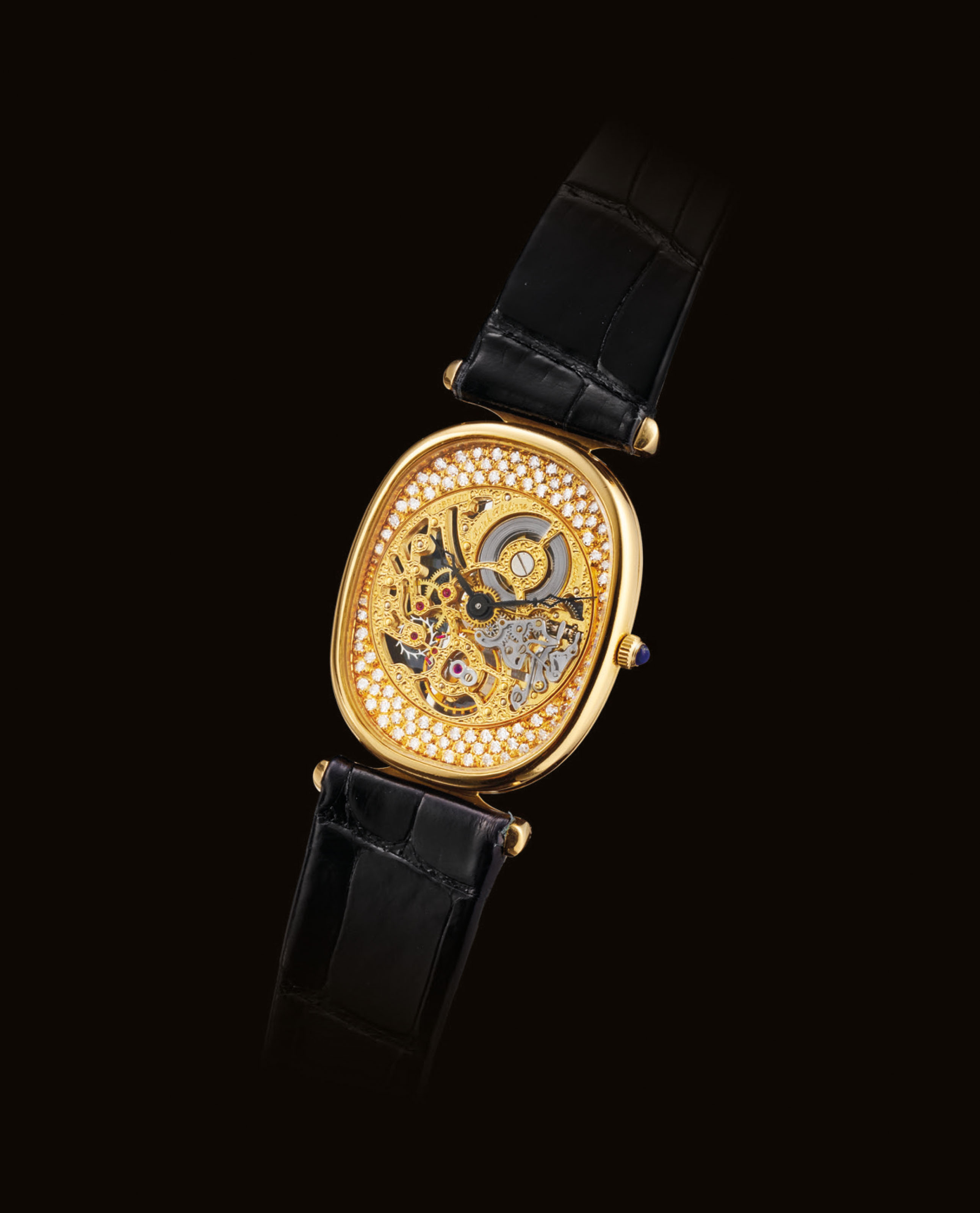 PATEK PHILIPPE. A FINE AND RARE 18K GOLD AND DIAMOND-SET CUSHION-SHAPED SKELETONISED WRISTWATCH
