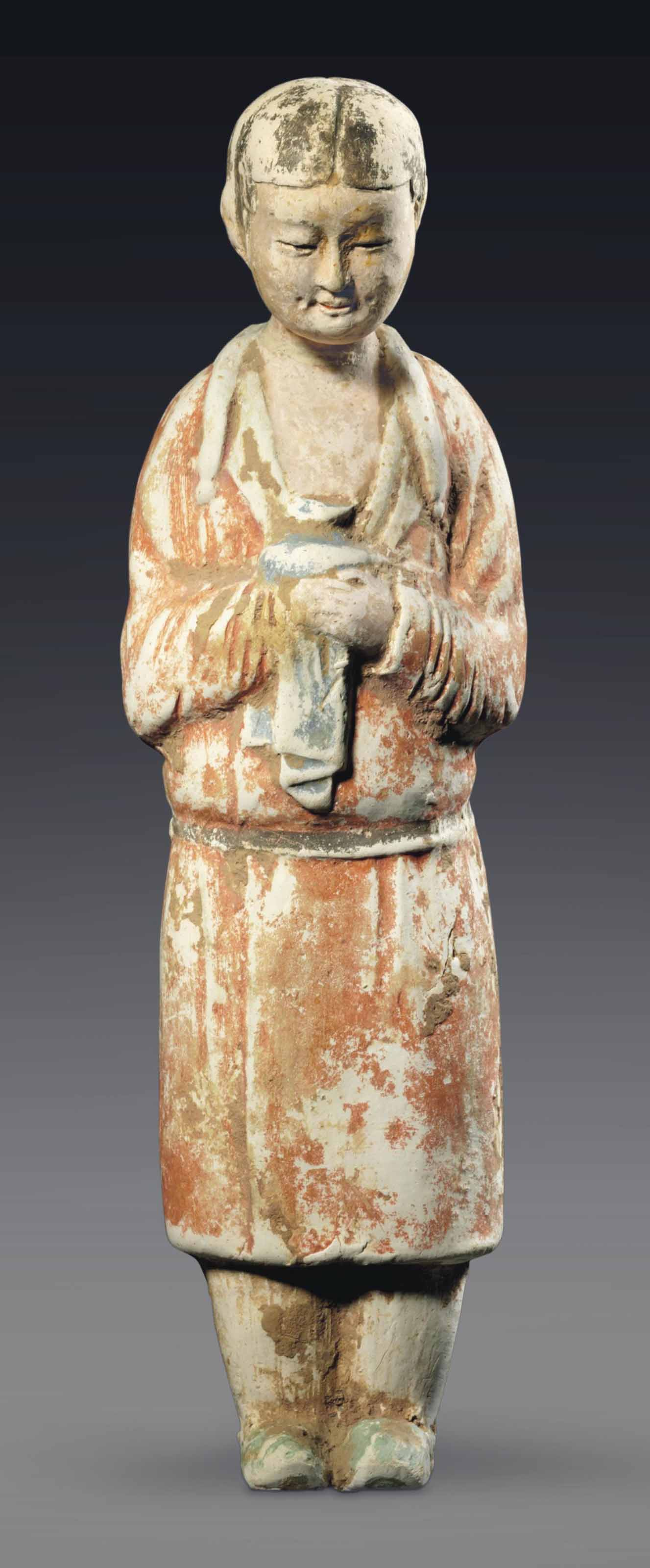 A RARE PAINTED POTTERY FIGURE OF A FEMALE ATTENDANT