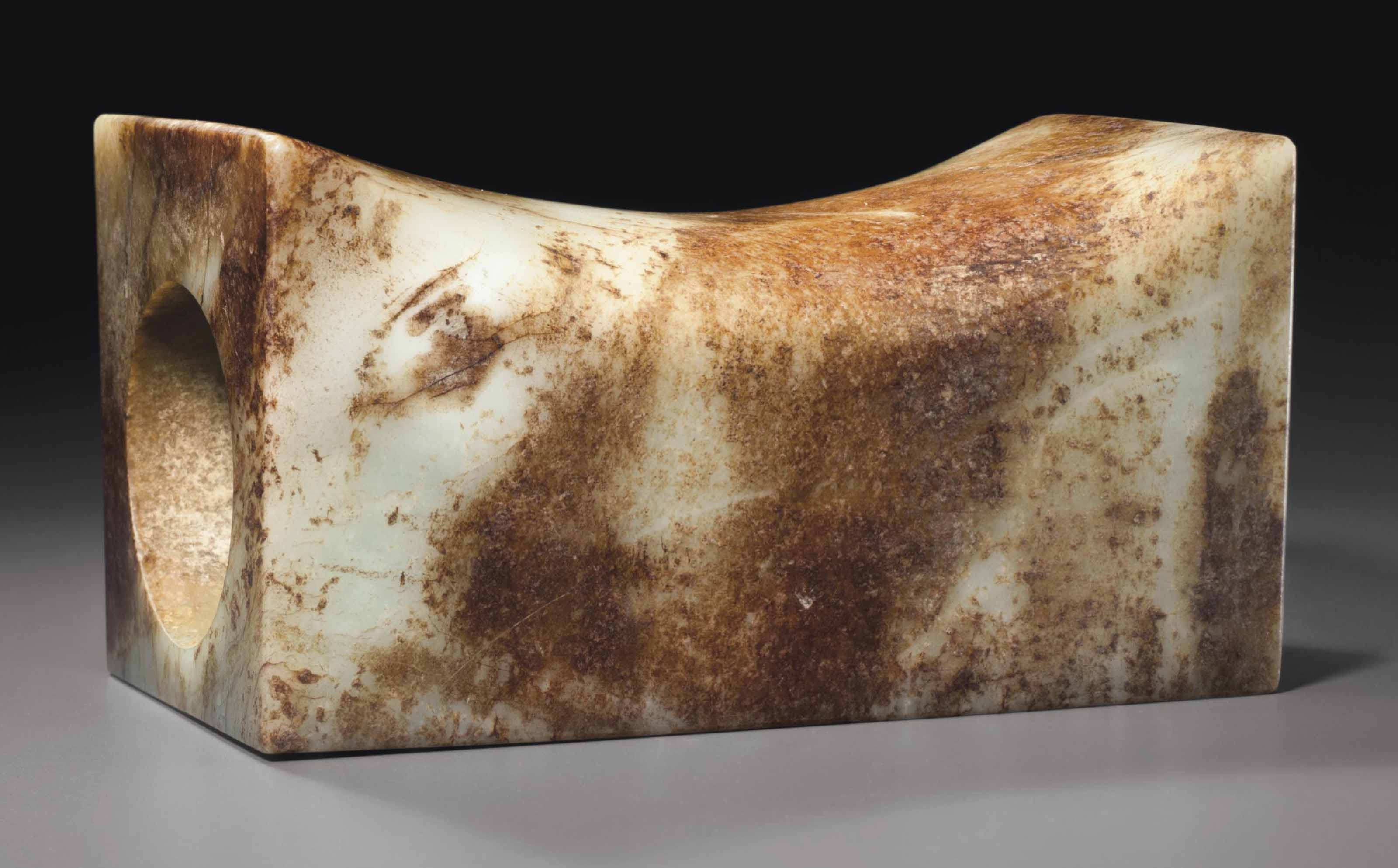 A WHITE AND RUSSET-STAINED WHITE JADE PILLOW