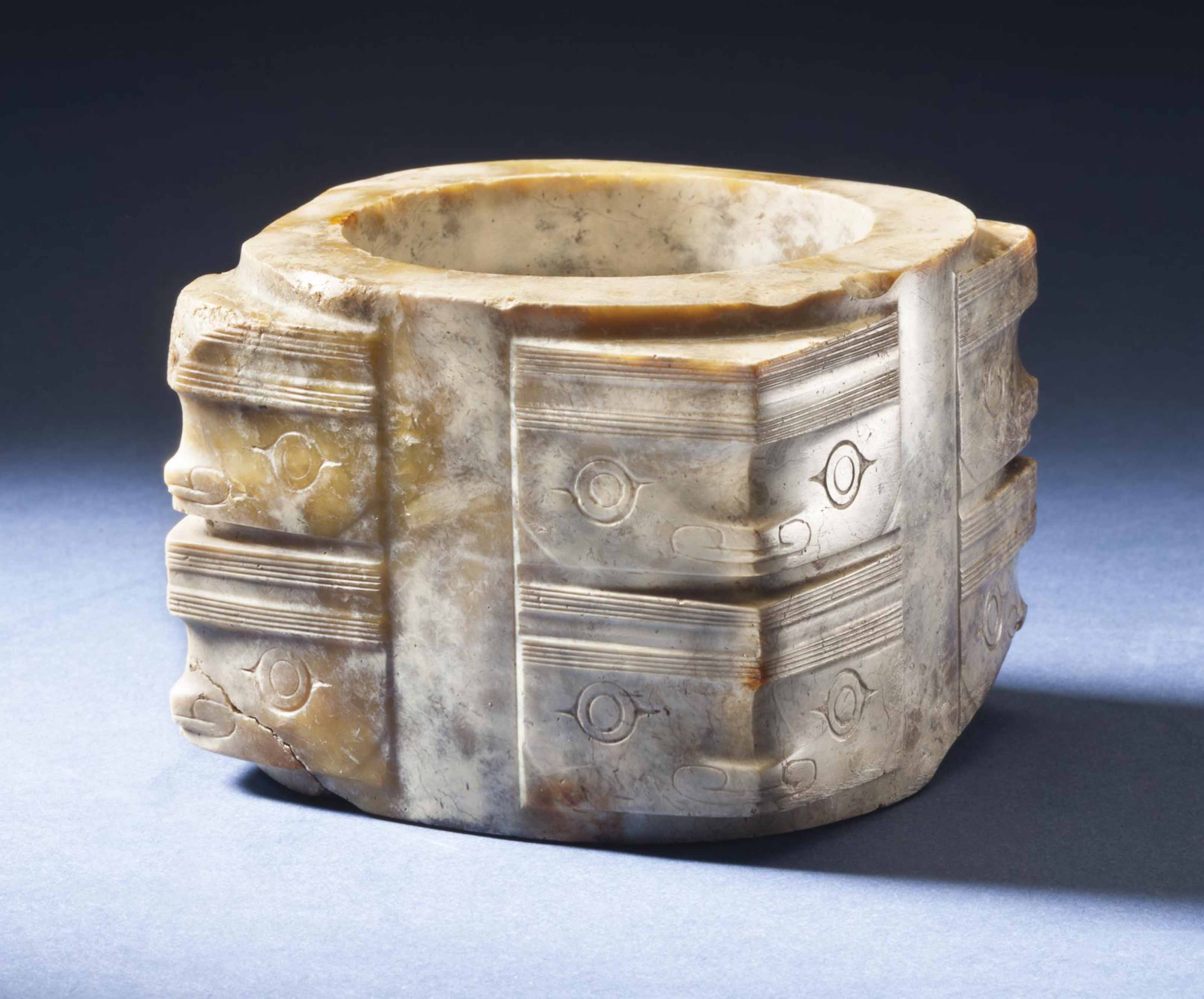 A RARE AND FINELY CARVED MOTTLED OPAQUE JADE CONG