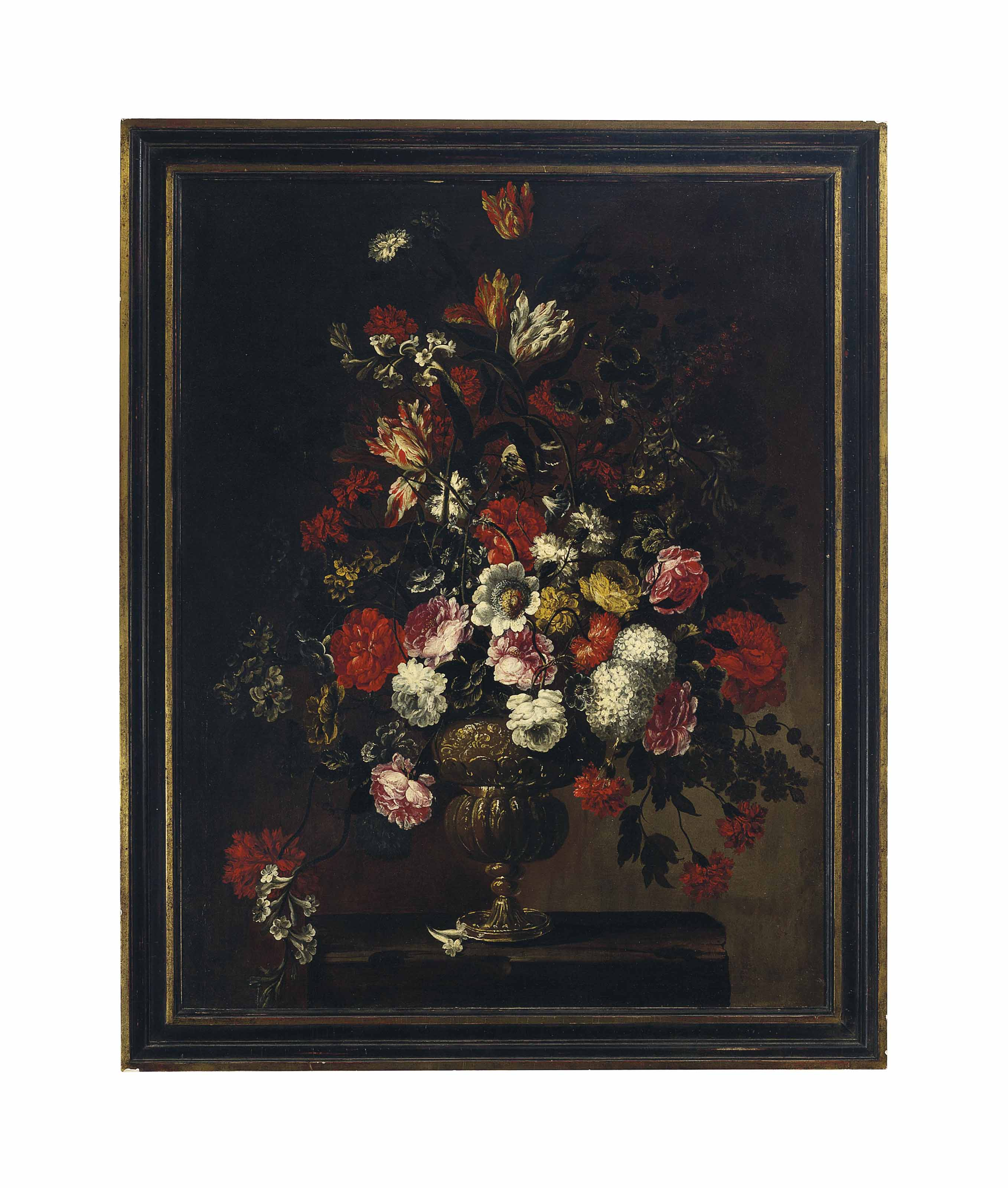 Roses, hydrangea, tulips and other flowers in an urn sitting on a table