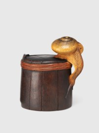 A WOOD NETSUKE OF A SNAIL ON A BUCKET