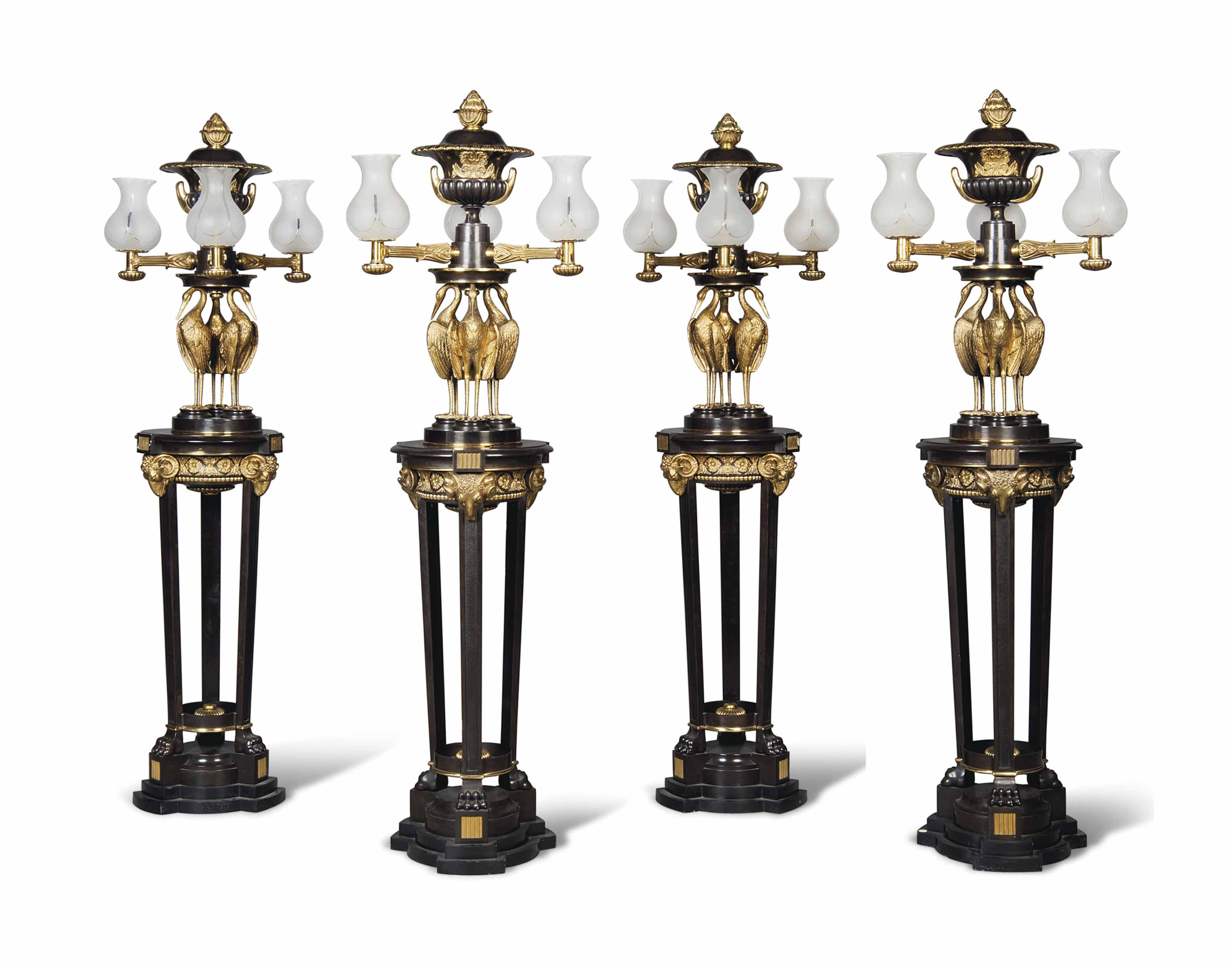 A SET OF FOUR ENGLISH ORMOLU AND PATINATED-BRONZE THREE-LIGHT TORCHERES