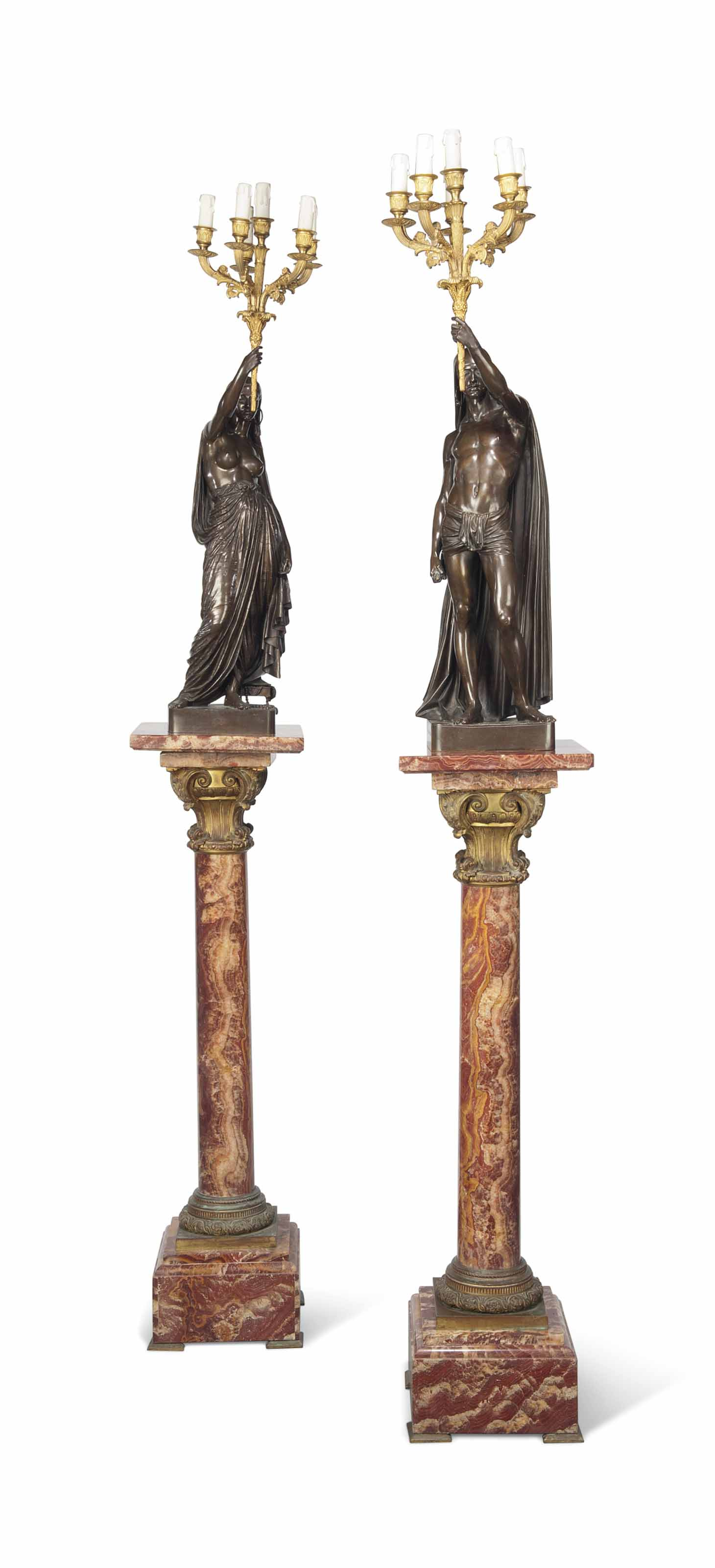 A PAIR OF FRENCH PATINATED-BRONZE FIGURAL TORCHERES TITLED 'UN ESCLAVE INDIEN PORTANT UNE TORCHE' AND 'UNE ESCLAVE INDIENNE PORTANT UNE TORCHE', ON ORMOLU-MOUNTED ALABASTER PEDESTALS