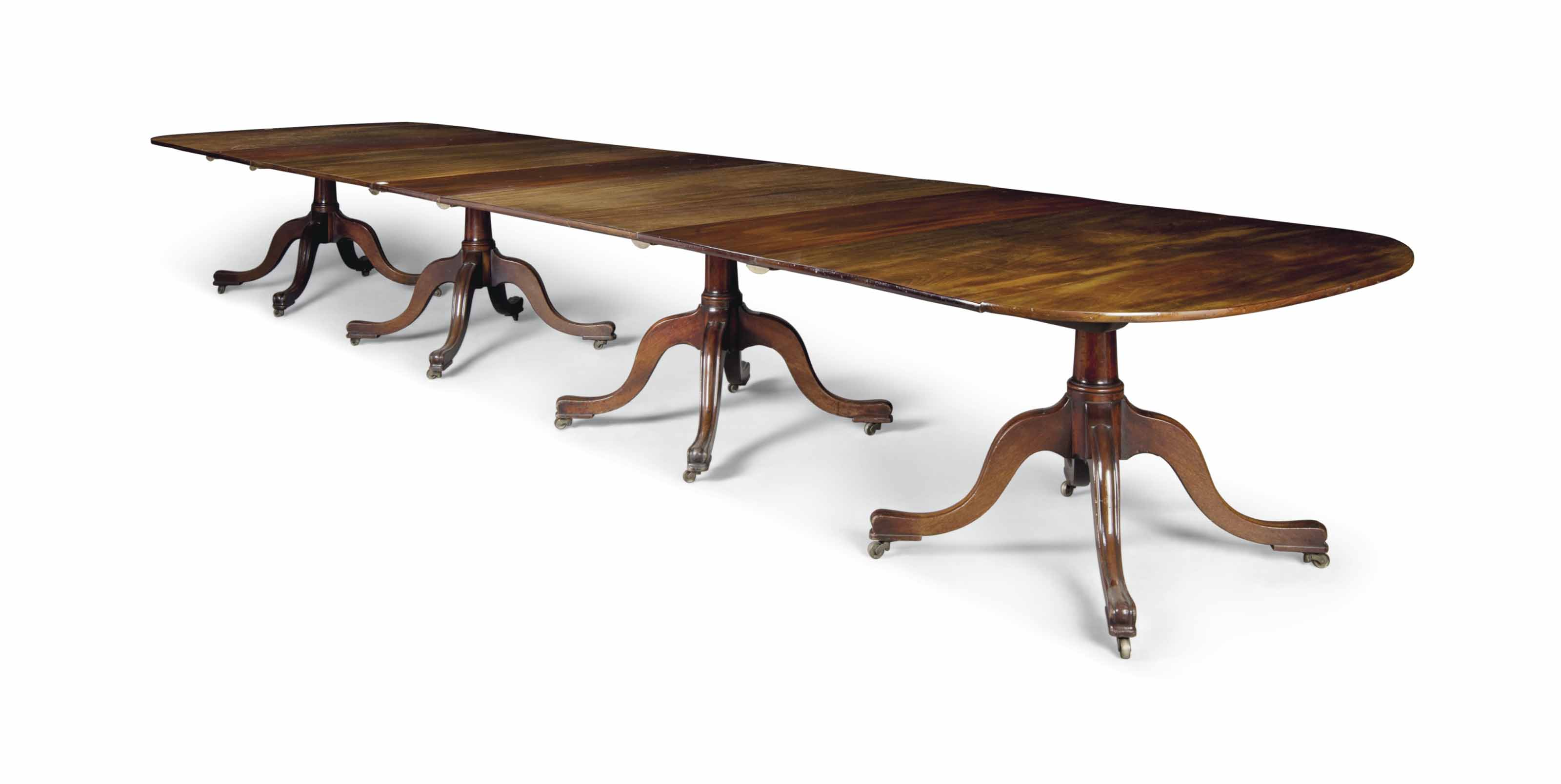 A GEORGE III MAHOGANY FOUR PEDESTAL DINING-TABLE
