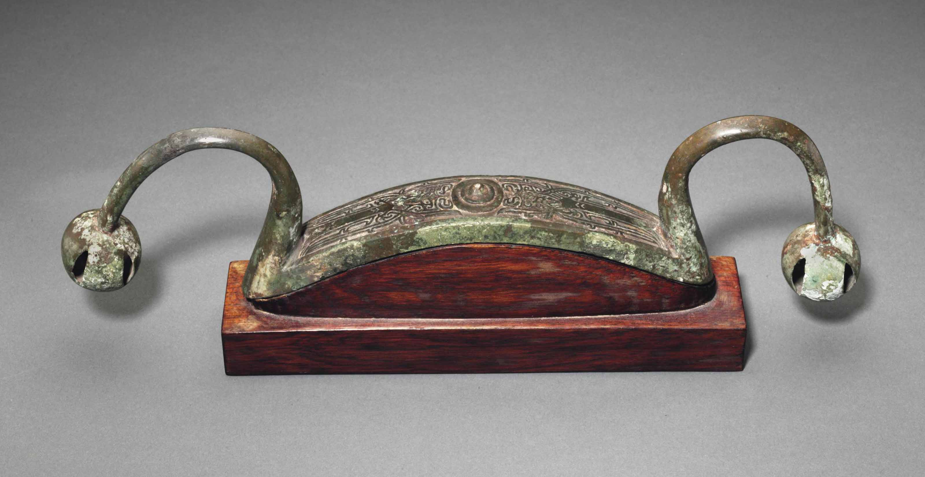 A BRONZE BOW-SHAPED FITTING WI