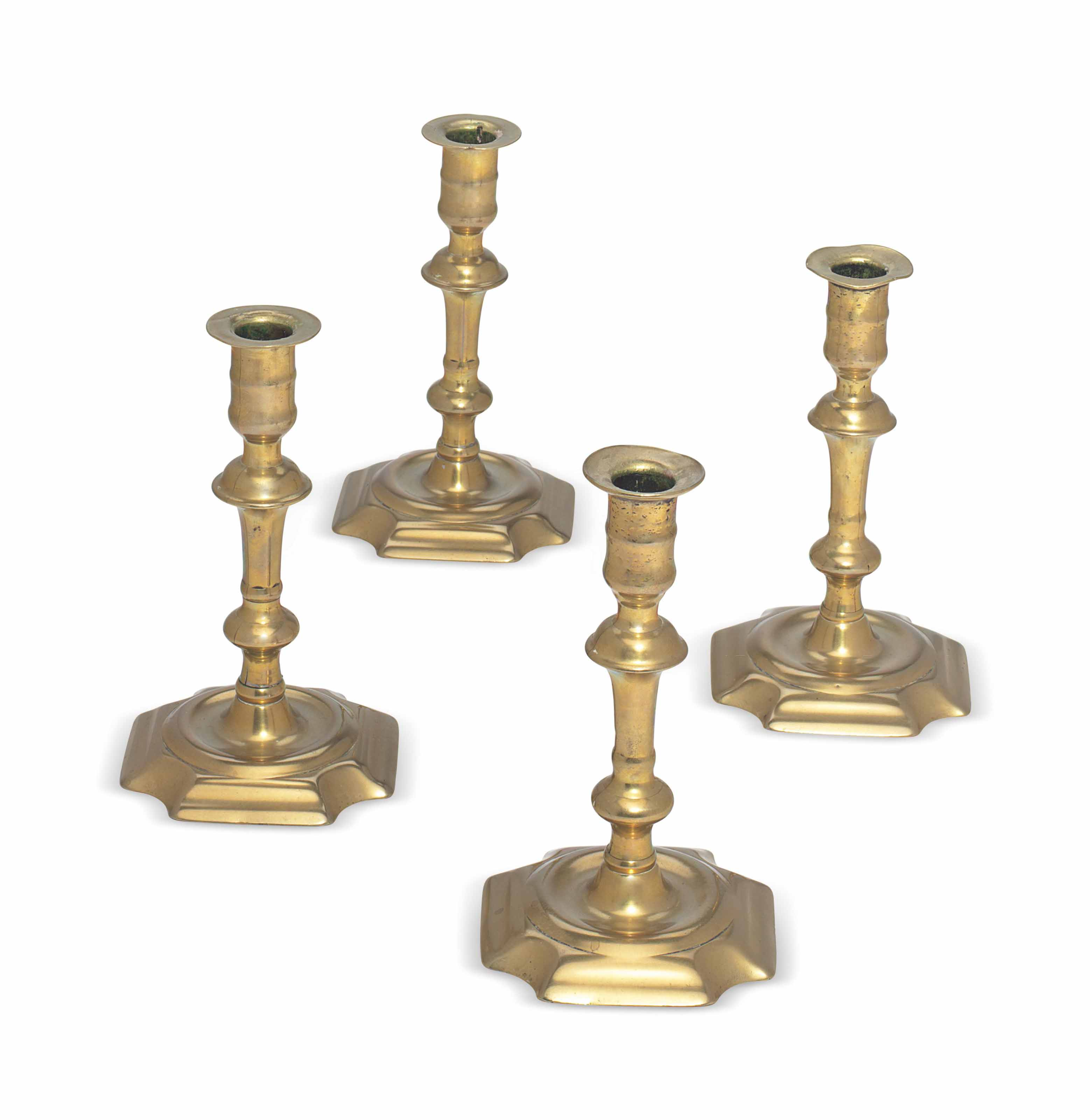 A SET OF FOUR NEARLY IDENTICAL GEORGE II CAST BRASS CANDLESTICKS