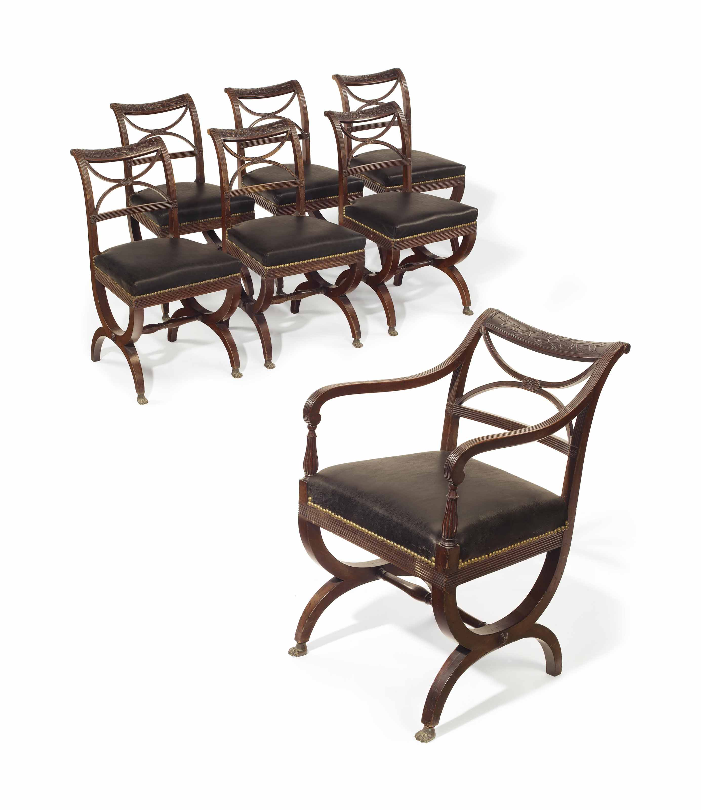 THE COSTER FAMILY SET OF SEVEN CLASSICAL CARVED MAHOGANY CURULE-BASE DINING CHAIRS
