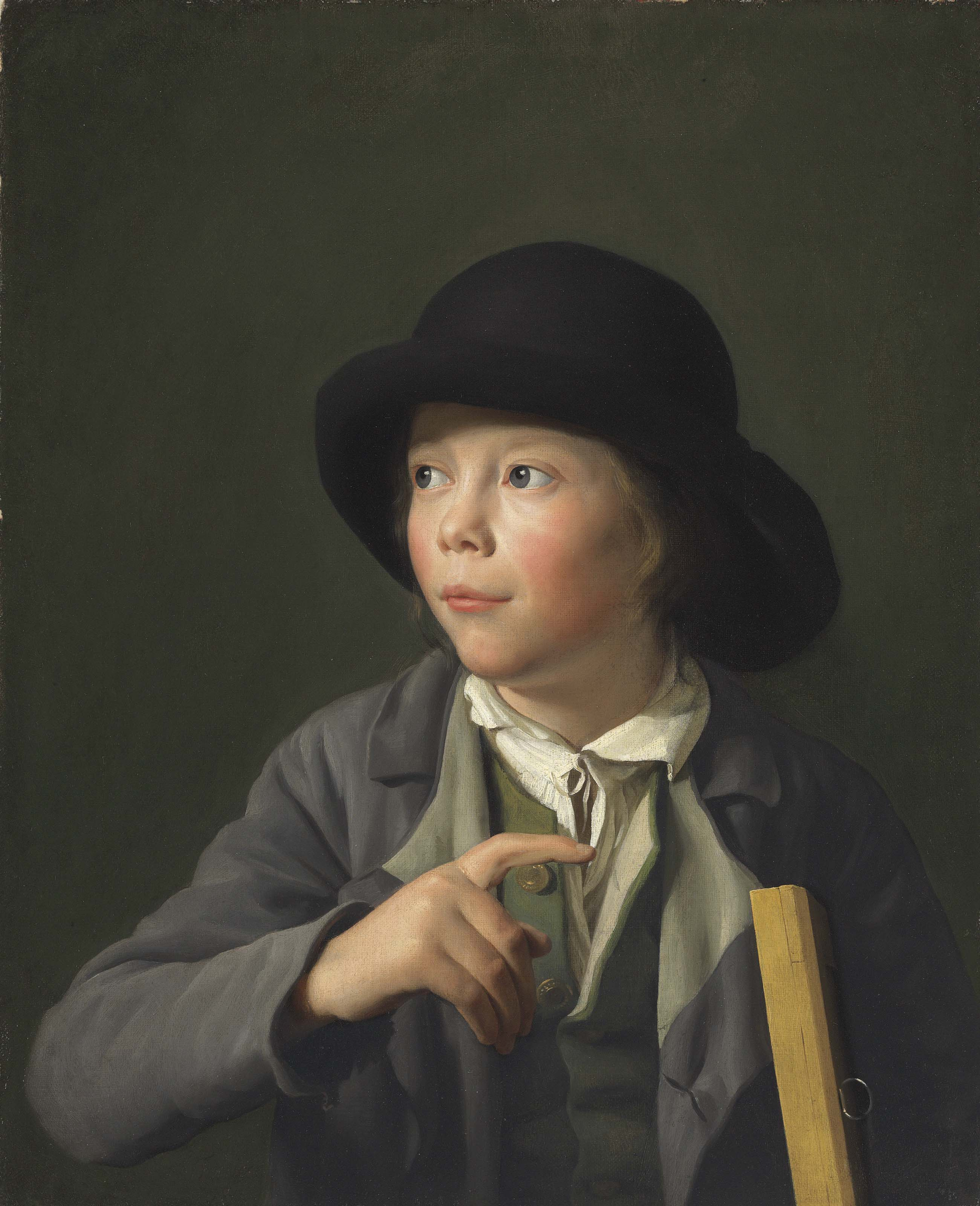 A youth wearing a hat and holding a picture