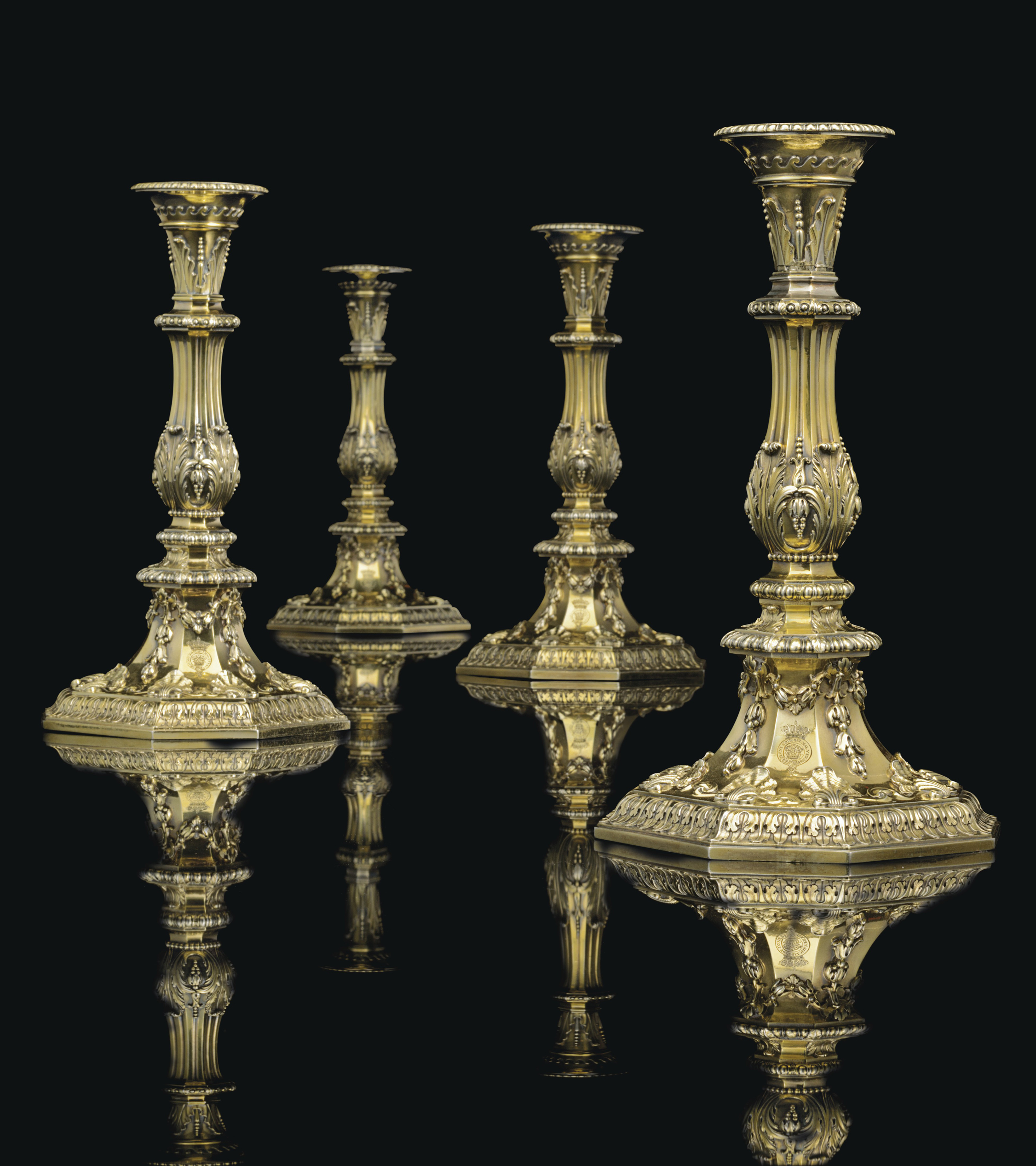 A SET OF FOUR GEORGE II SILVER-GILT CANDLESTICKS