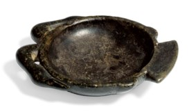 AN EGYPTIAN BLACK STEATITE COSMETIC PALETTE