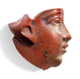 AN EGYPTIAN RED GLASS FACE INLAY