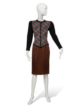 A KNITTED JACKET AND A BROWN SATIN SKIRT