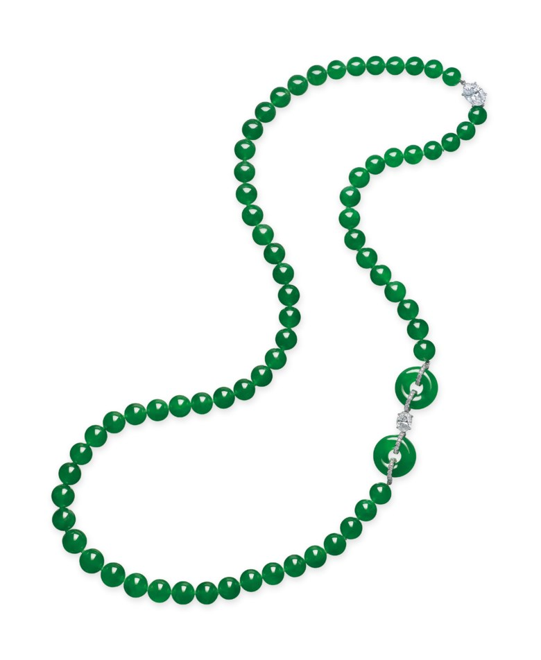 A Jadeite and Diamond Necklace. Composed of sixty-nine jadeite beads, measuring approximately 8.2 to 10.8 mm, spaced by a pair of jadeite hoops and an oval-shaped diamond, weighing approximately 1.50 carats, to the similarly-cut diamond clasp, weighing approximately 3.02 carats, mounted in platinum, largest hoop diameter approximately 18.6 mm, thickness approximately 6.8 mm, necklace 73.5 cm. Sold