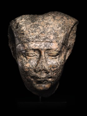 AN EGYPTIAN MONUMENTAL RED GRANITE HEAD OF PHARAOH NECTANEBO II