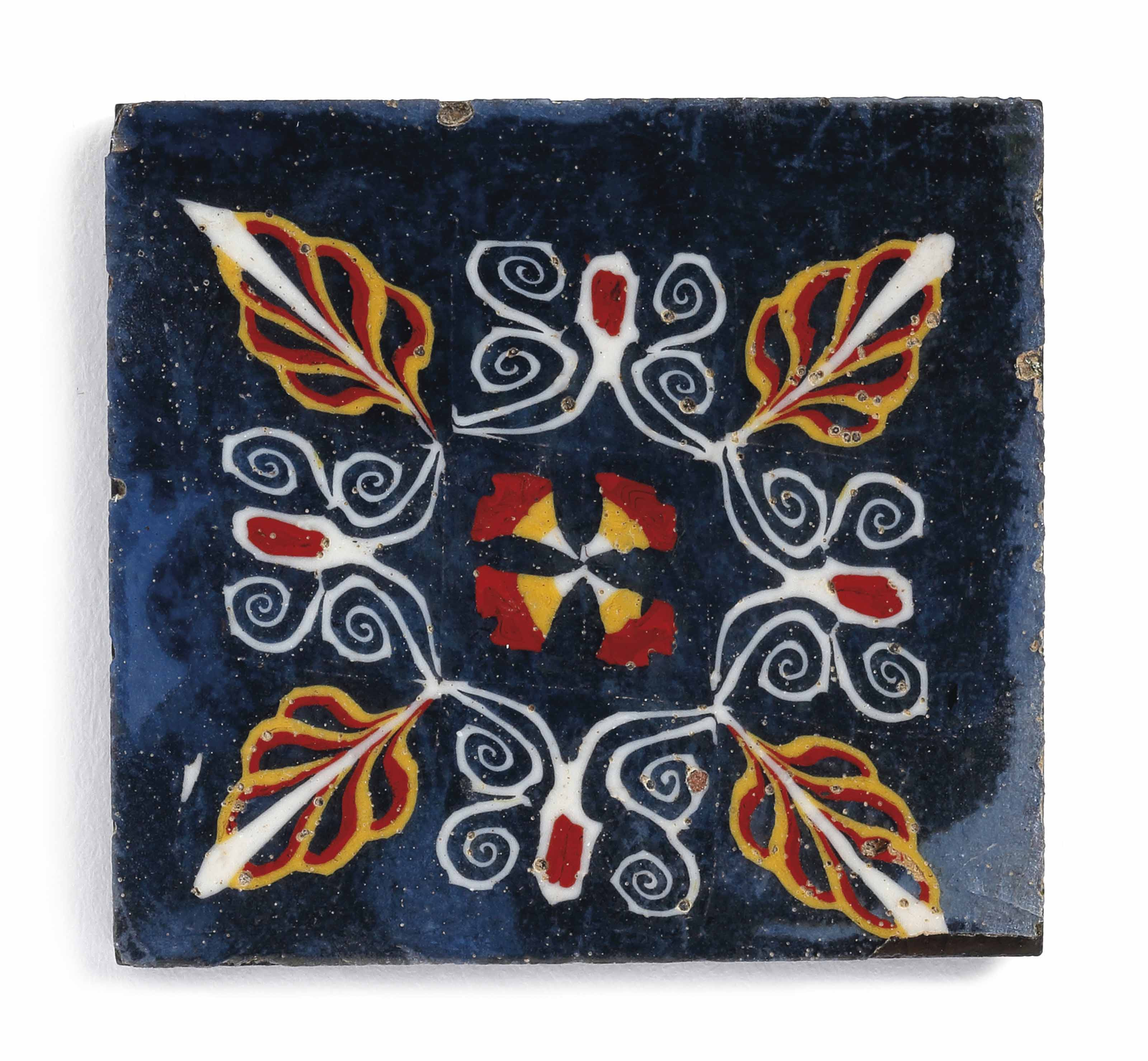 AN EGYPTIAN MOSAIC GLASS INLAY PLAQUE WITH LILY-AND-PALMETTE MOTIF