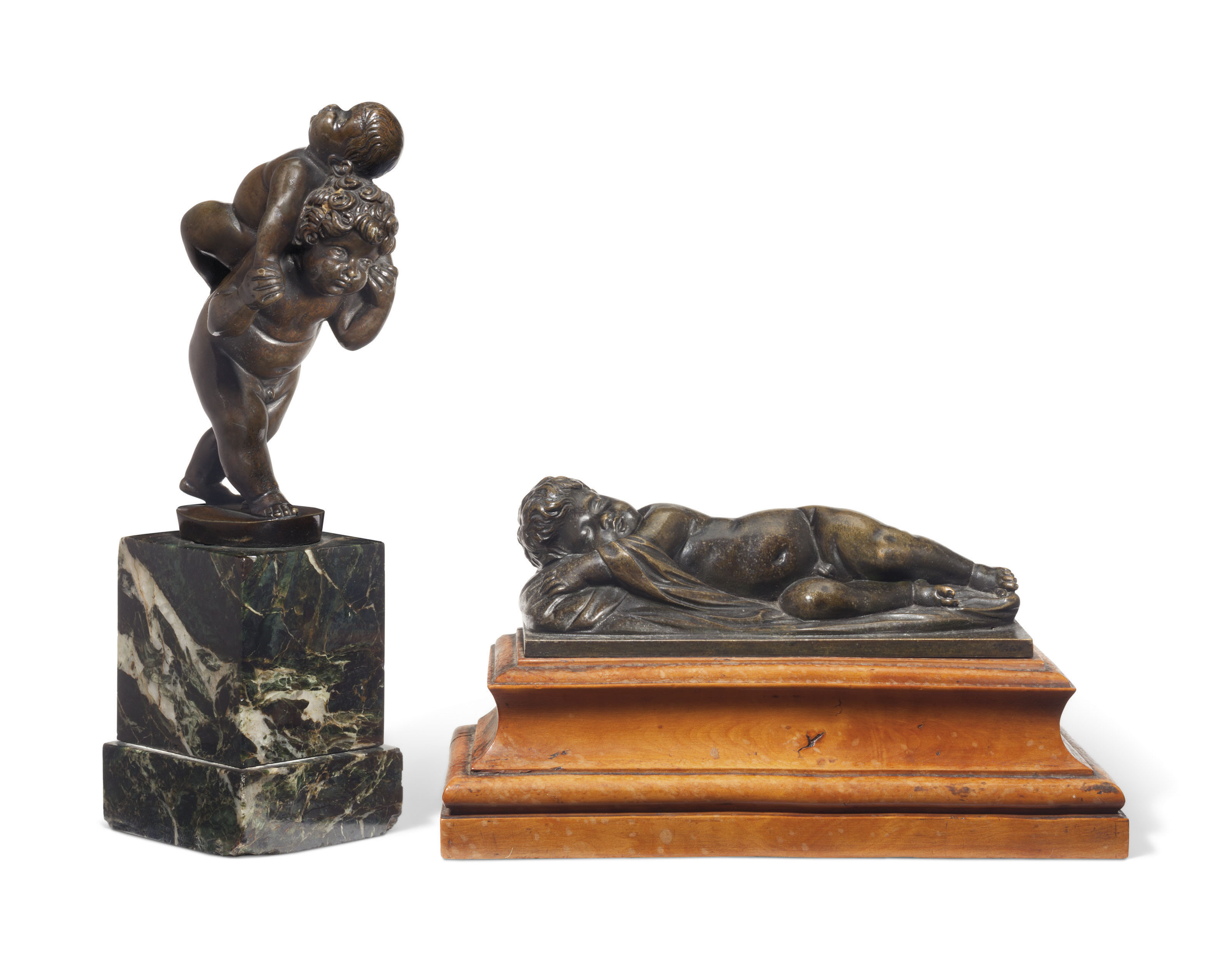 A BRONZE GROUP OF A CHILD CARRYING ANOTHER CHILD ON HIS BACK, TOGETHER WITH A BRONZE MODEL OF A SLEEPING CHILD