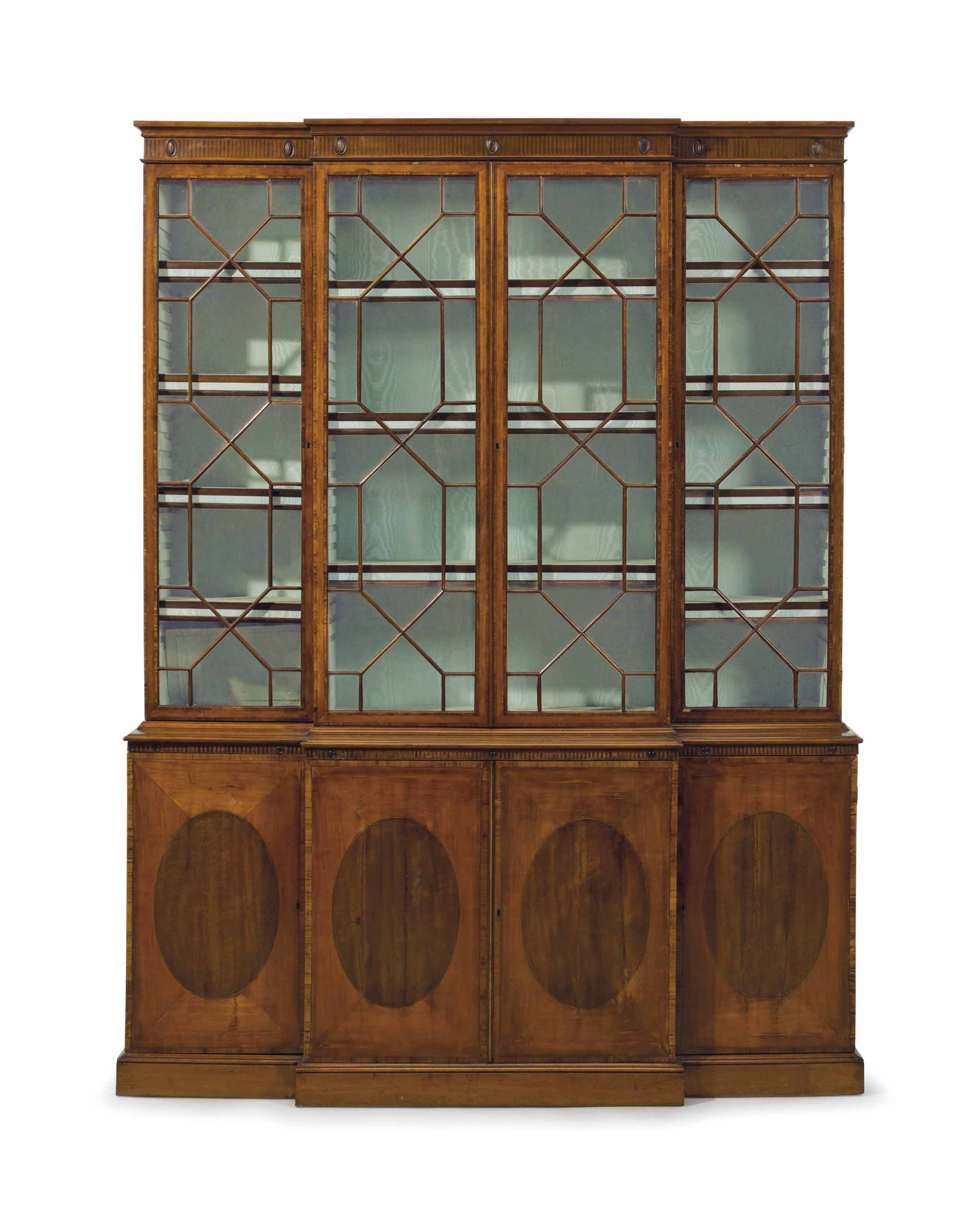 A GEORGE III SATINWOOD, PADOUK AND TULIPWOOD BREAKFRONT BOOKCASE