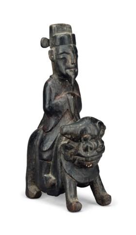 A KOREAN WOOD FIGURE OF A MAN RIDING A LION