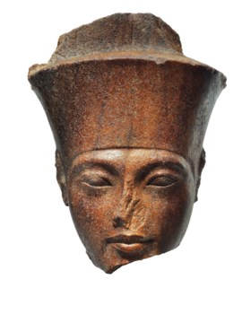 AN EGYPTIAN BROWN QUARTZITE HEAD OF THE GOD AMEN WITH THE FE