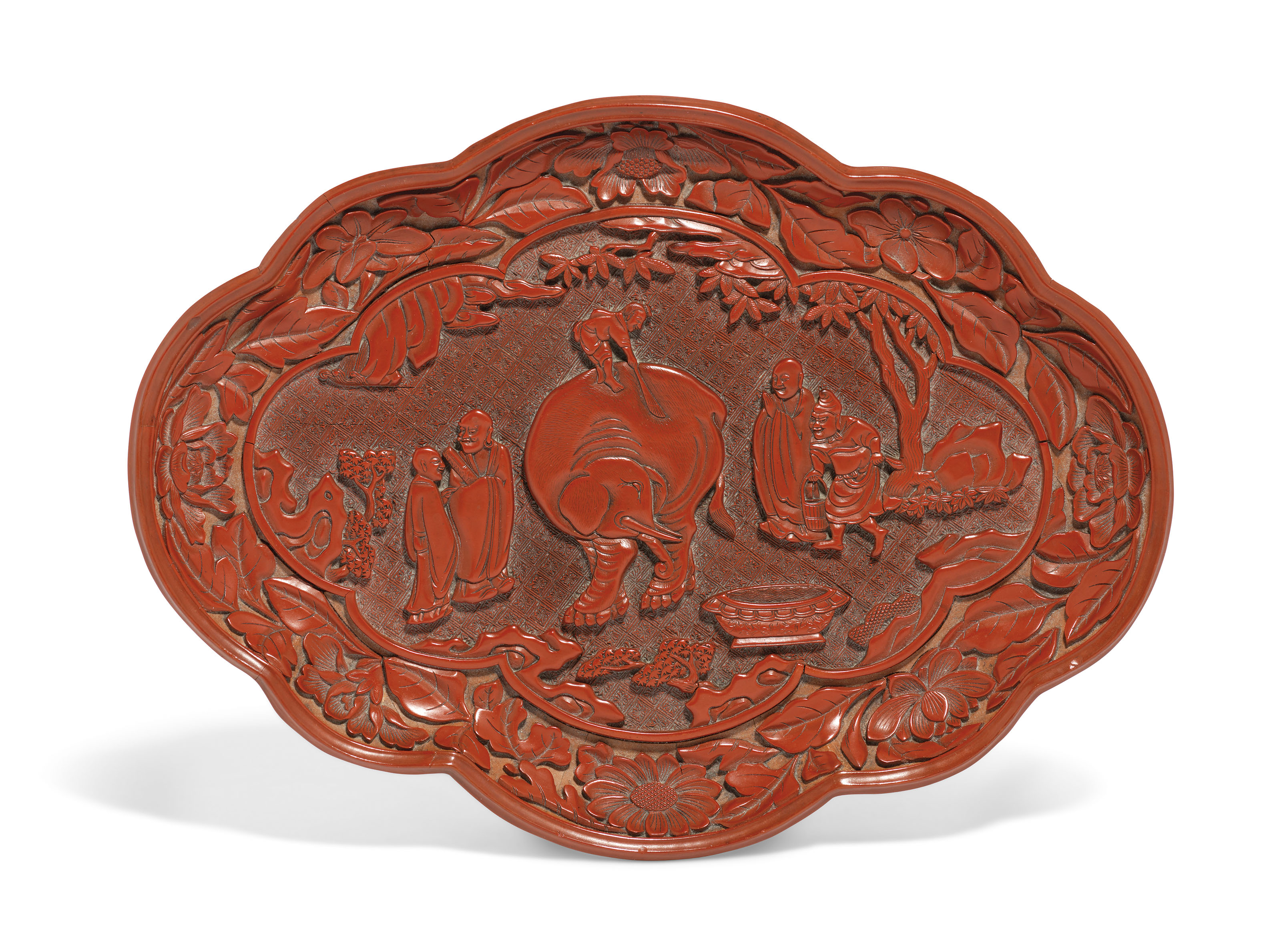 A RARE AND FINELY CARVED LOBED CINNABAR LACQUER 'WASHING THE ELEPHANT' DISH