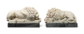 A PAIR OF CARVED MARBLE RECLINING LIONS