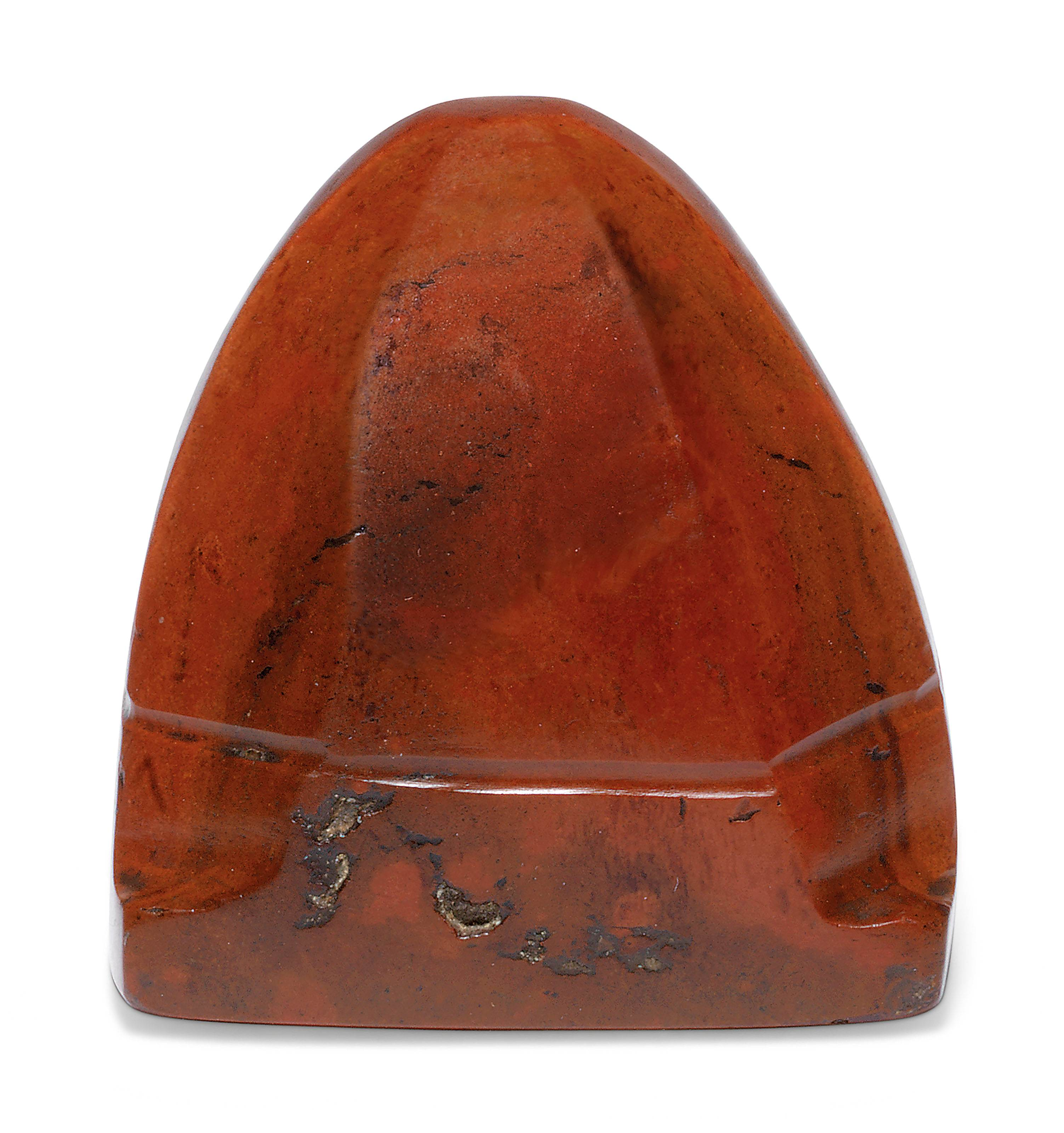 A FACETTED AND DOMED RED JASPER IMPLEMENT