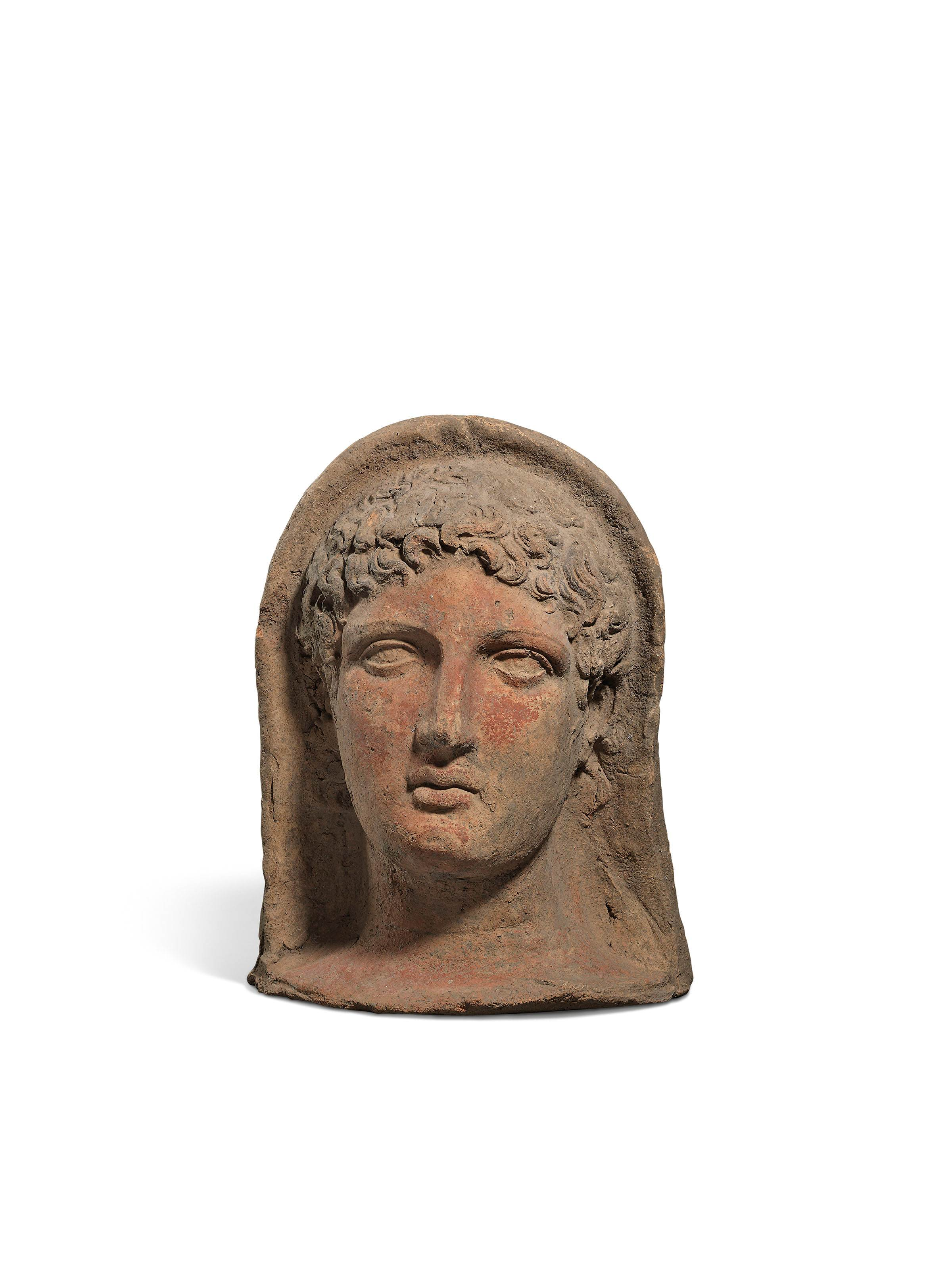 AN ETRUSCAN TERRACOTTA VOTIVE HEAD OF A YOUTH
