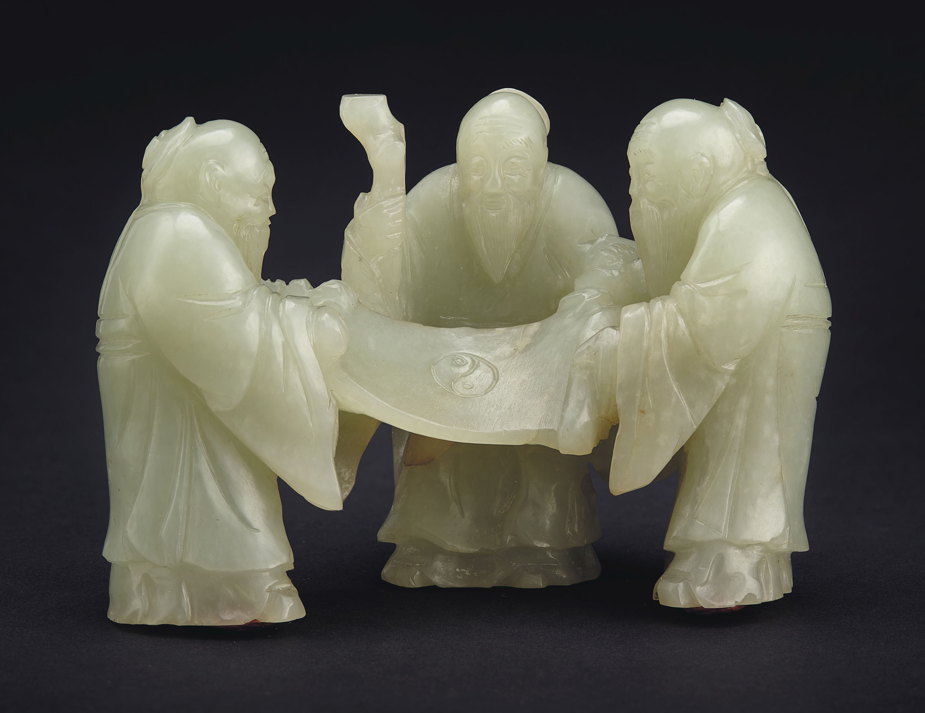 A PALE GREYISH-GREEN JADE CARVING OF THREE SCHOLARS